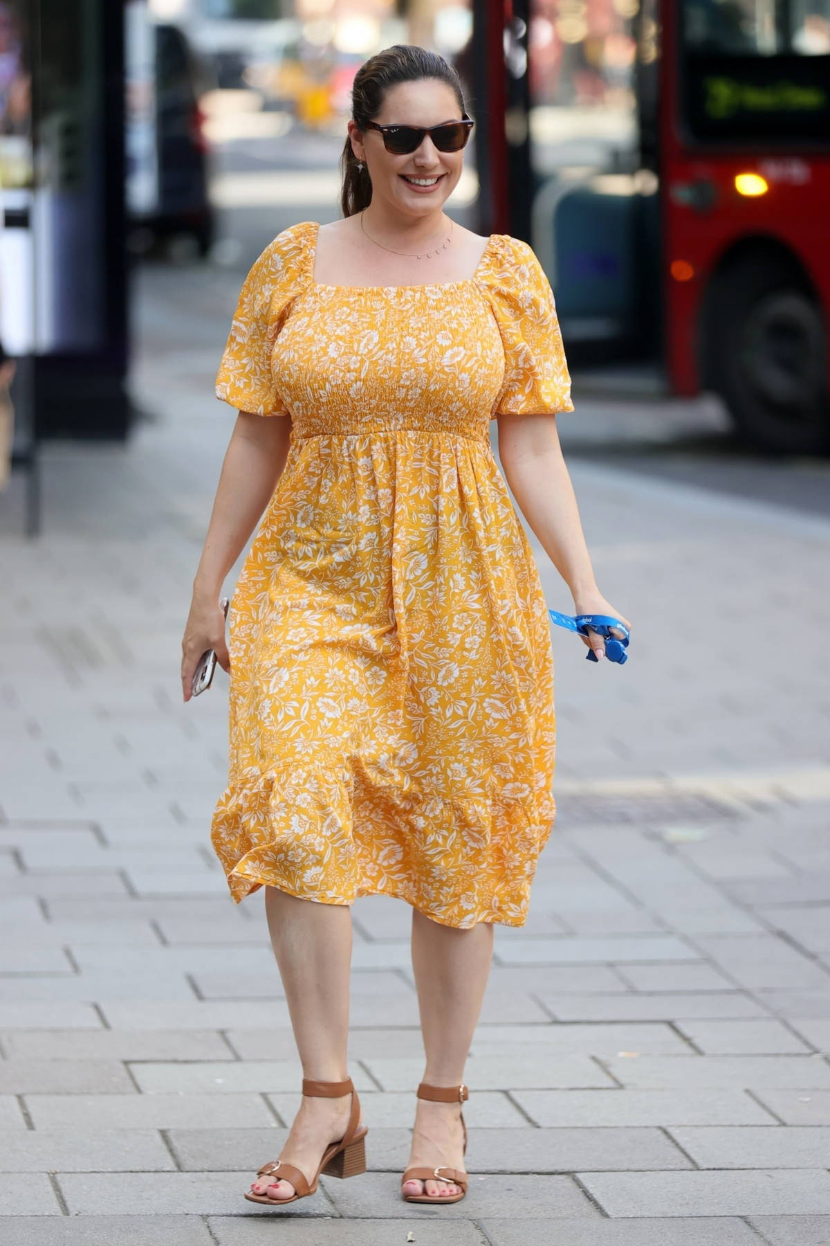 Kelly Brook looks radiant in a yellow summer dress as she arrives at Heart radio in London, UK