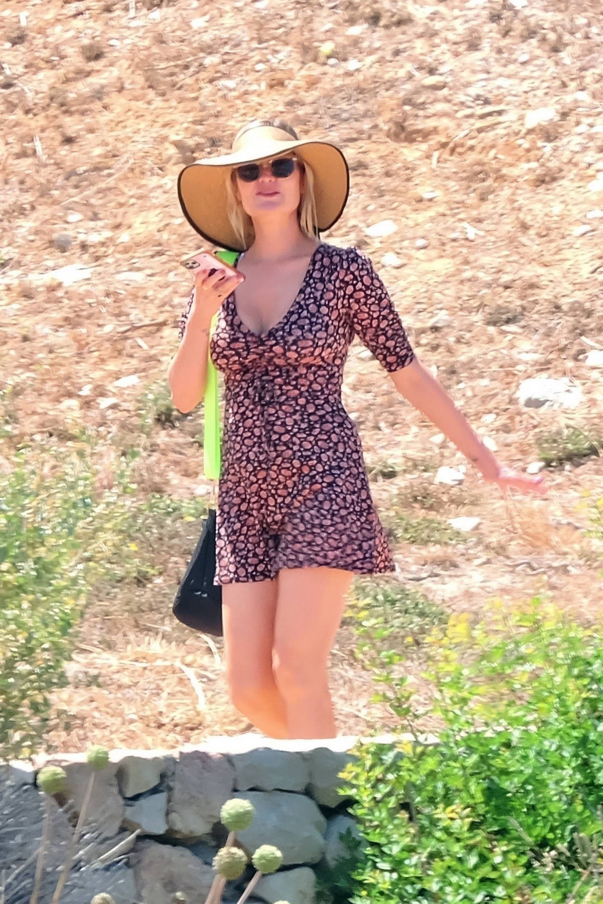 Laura Whitmore wears a sunhat and floral print mini dress while stepping out in Majorca, Spain