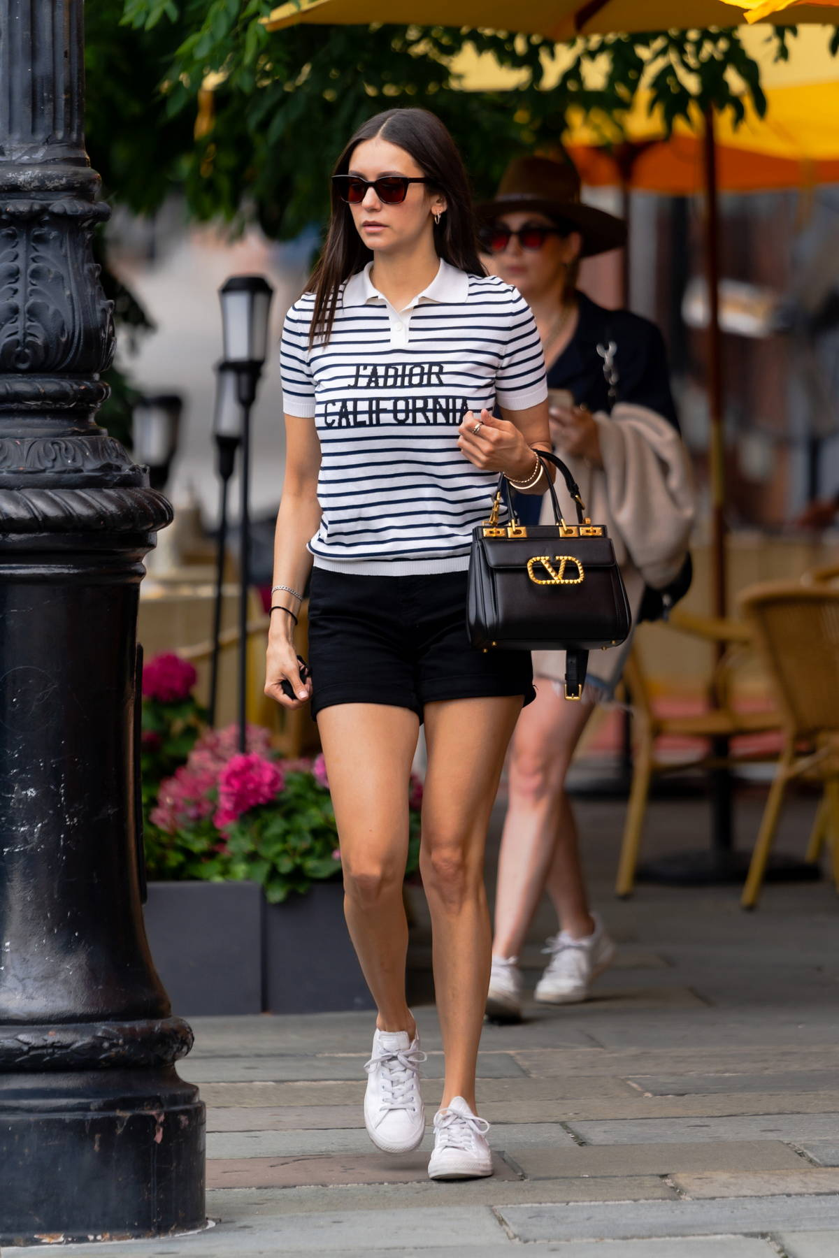 Nina Dobrev puts on a leggy display in black shorts paired with striped J'Adior California top while stepping out in New York City