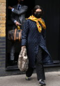 Bella Hadid looks chic in a black quilted coat and yellow scarf while leaving her hotel in London, UK