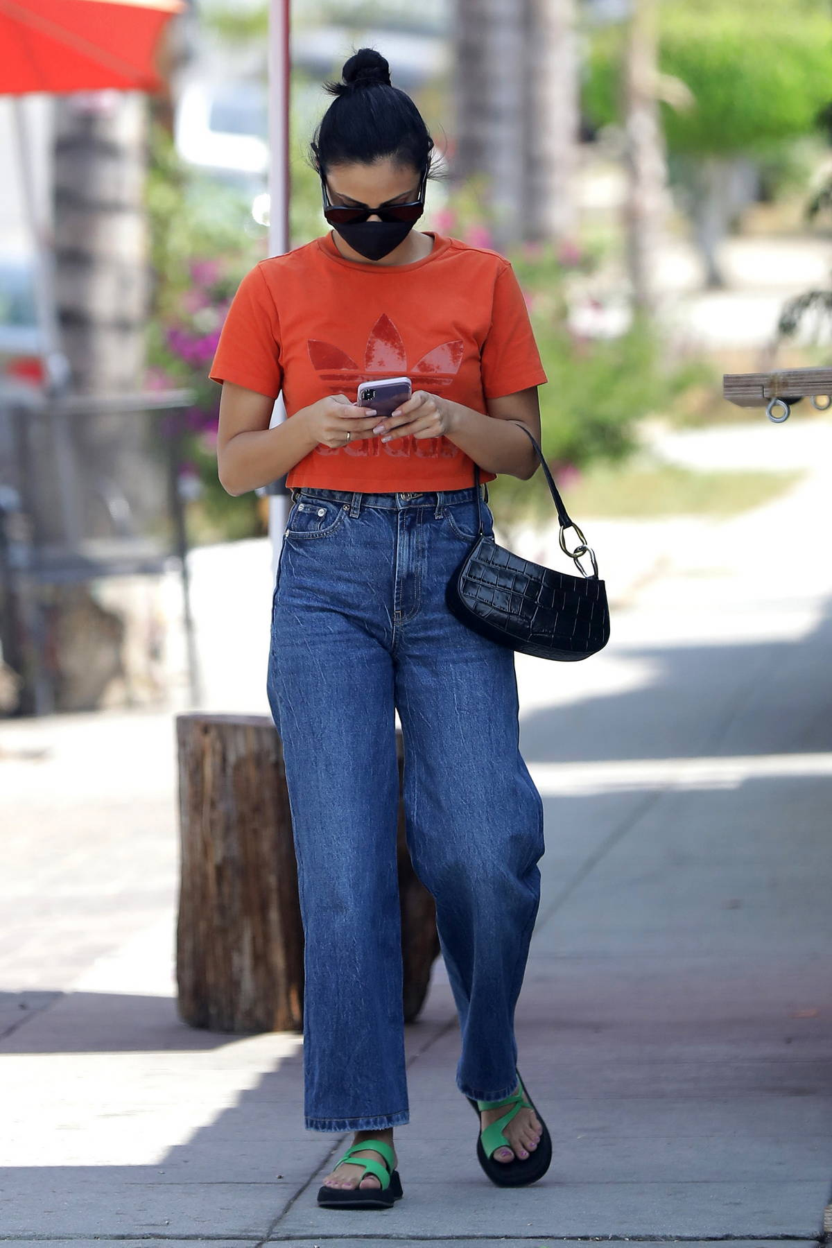 Camila Mendes goes casual in an orange Adidas tee and jeans while stepping out in Los Angeles