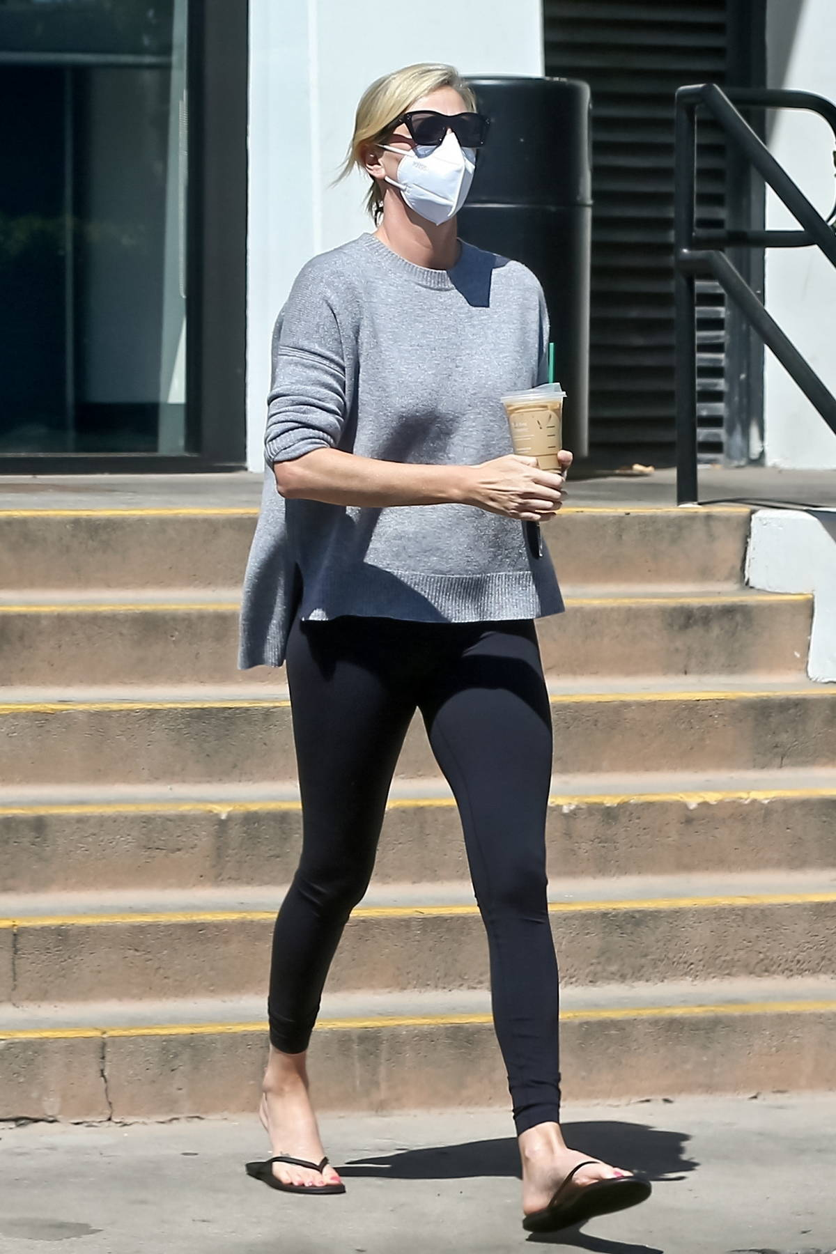 Charlize Theron opts for a grey sweatshirt and black leggings during a coffee run at Starbucks in West Hollywood, California
