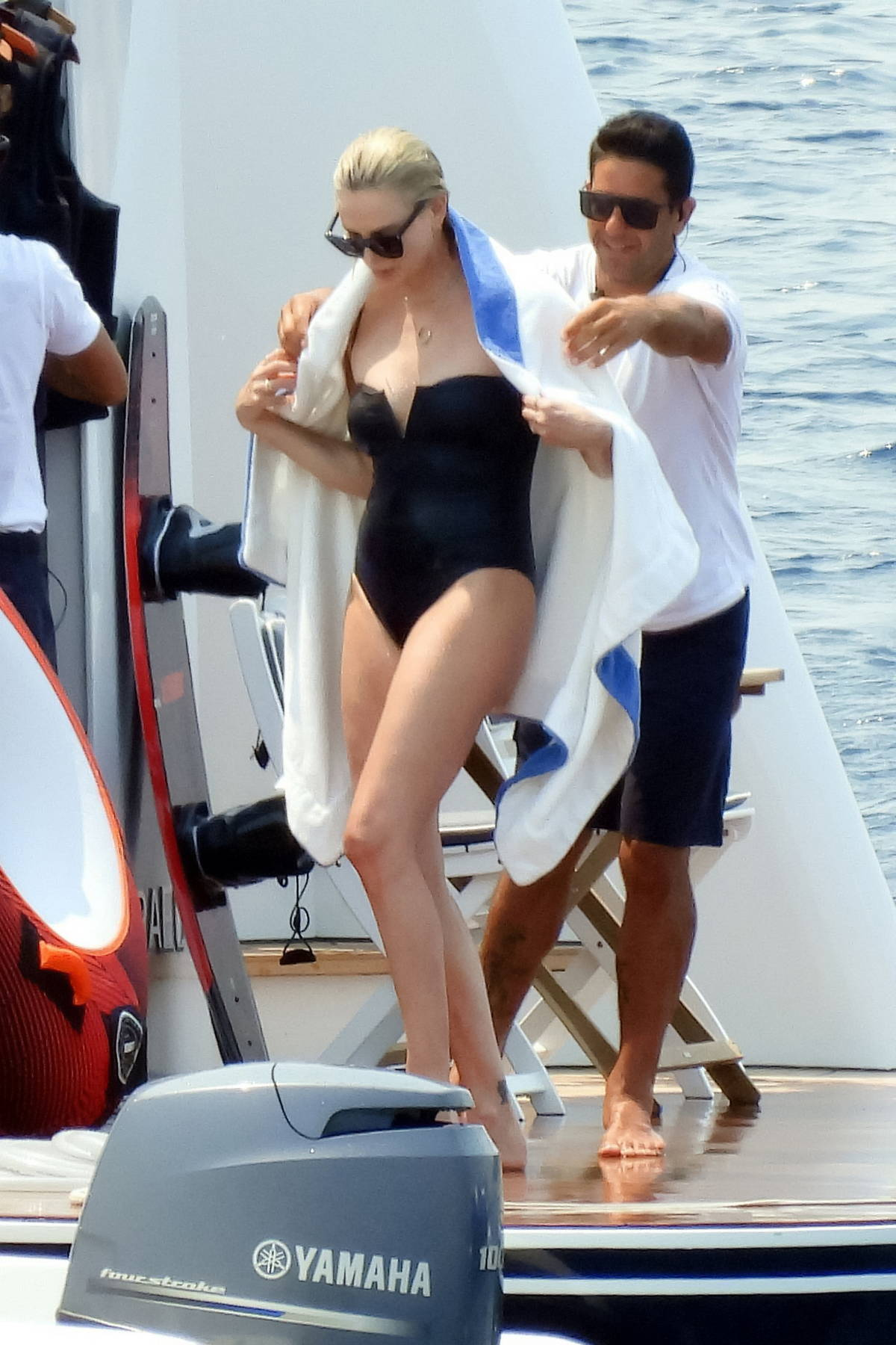 Charlize Theron slips into a black swimsuit during a boat trip with her family in Greece
