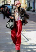 Dua Lipa rocks a Balenciaga leather jacket and red cargo pants while arriving at a hotel in London, UK