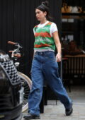 Dua Lipa wears a green sweater vest and jeans while heading to a studio in London, UK