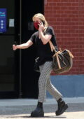 Emma Roberts wears checkered pants and black tee as she steps out carrying a Louis Vuitton duffel bag in New York City