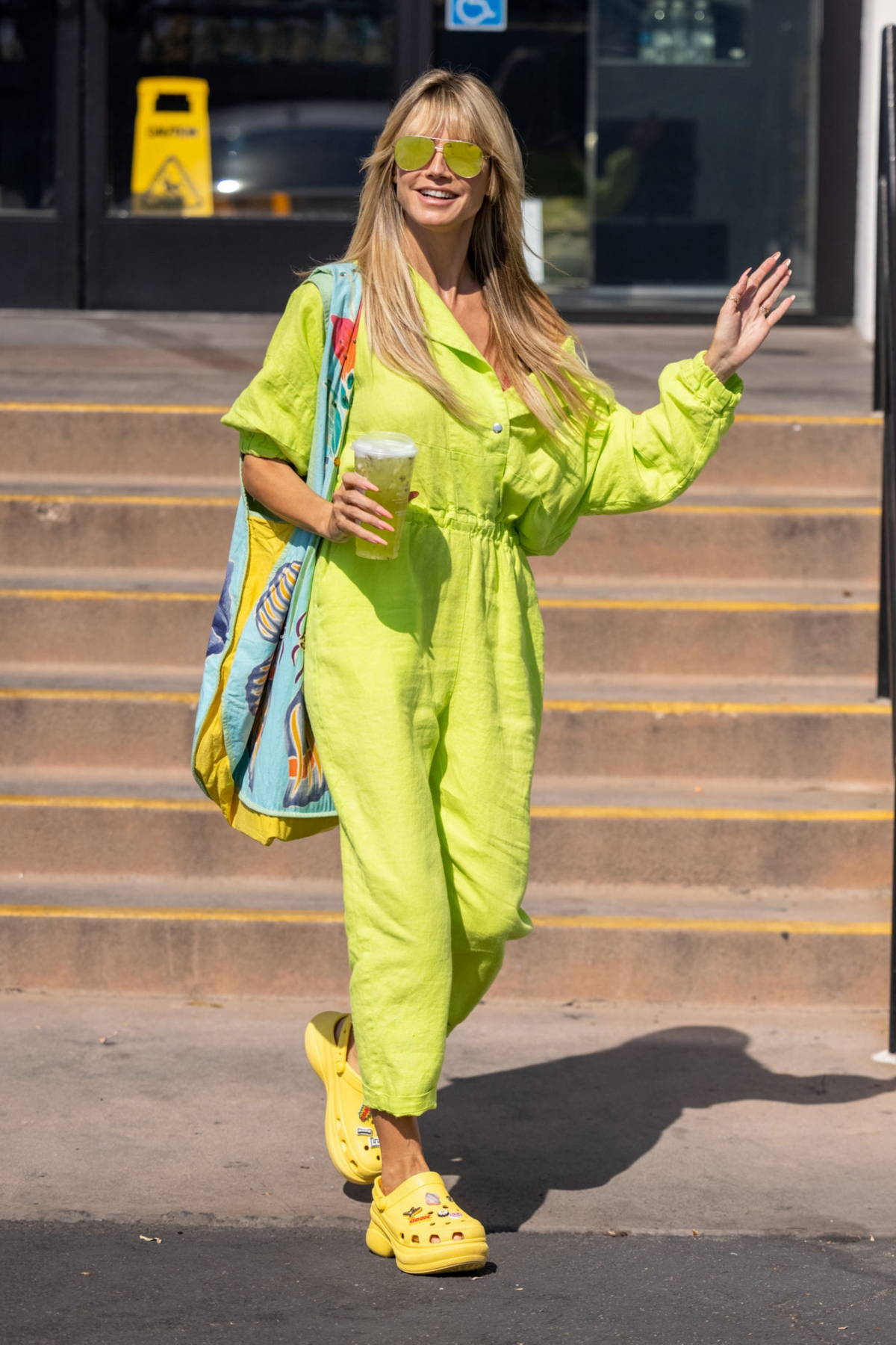 Heidi Klum stands out in a neon-green jumpsuit and yellow crocs while she grabs an iced drink at Starbucks in Los Angeles