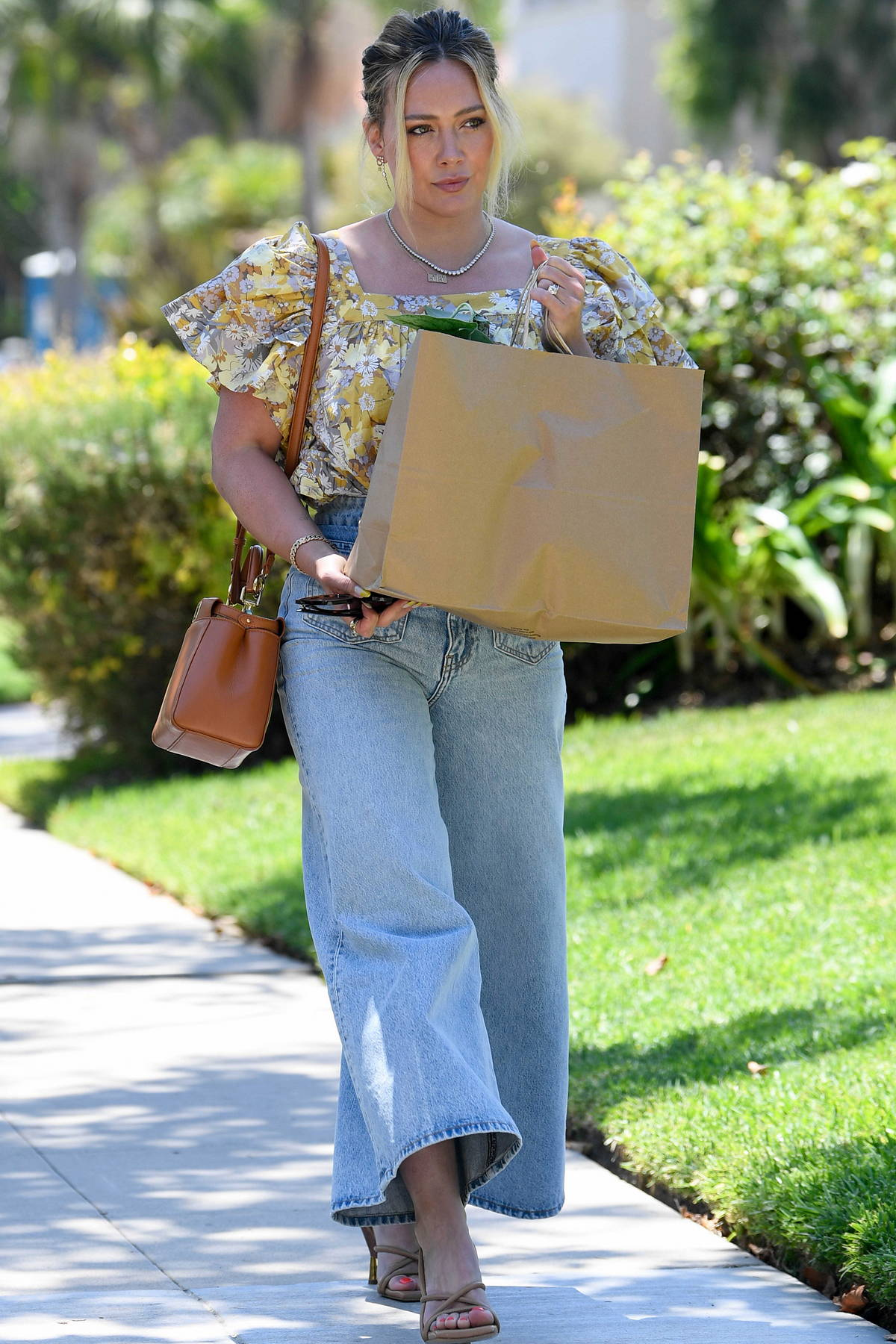 Hilary Duff looks fashionable in a floral top and flared jeans as she steps out to shop in Los Angeles