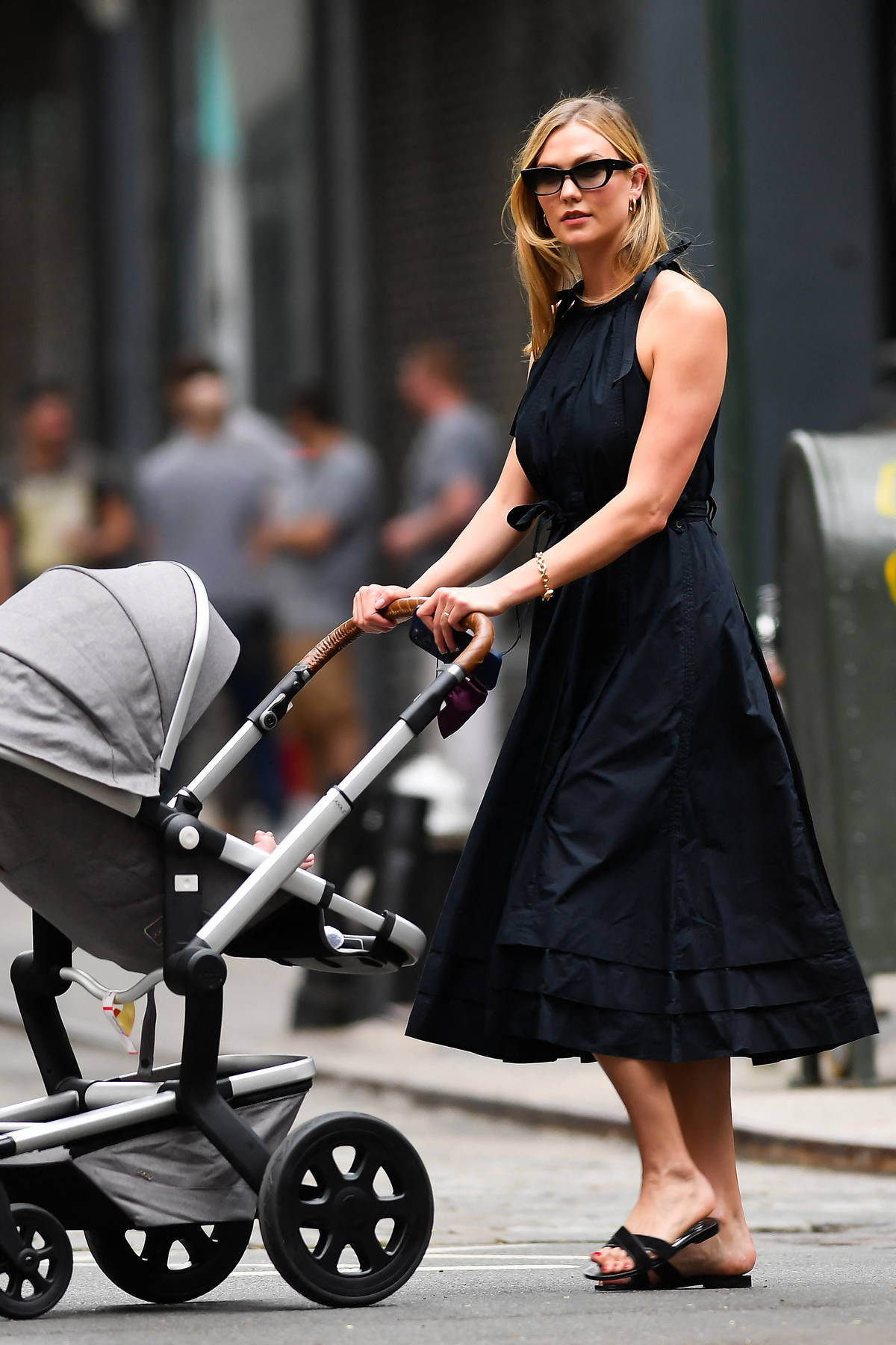 Karlie Kloss looks great in a black dress as she steps out for stroll with her baby in New York City