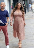 Kelly Brook is all smiles as she returns to work after her holiday in London, UK