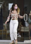 Lily James wears a floral print blouse and white denim pants while out shopping with friends in Los Angeles