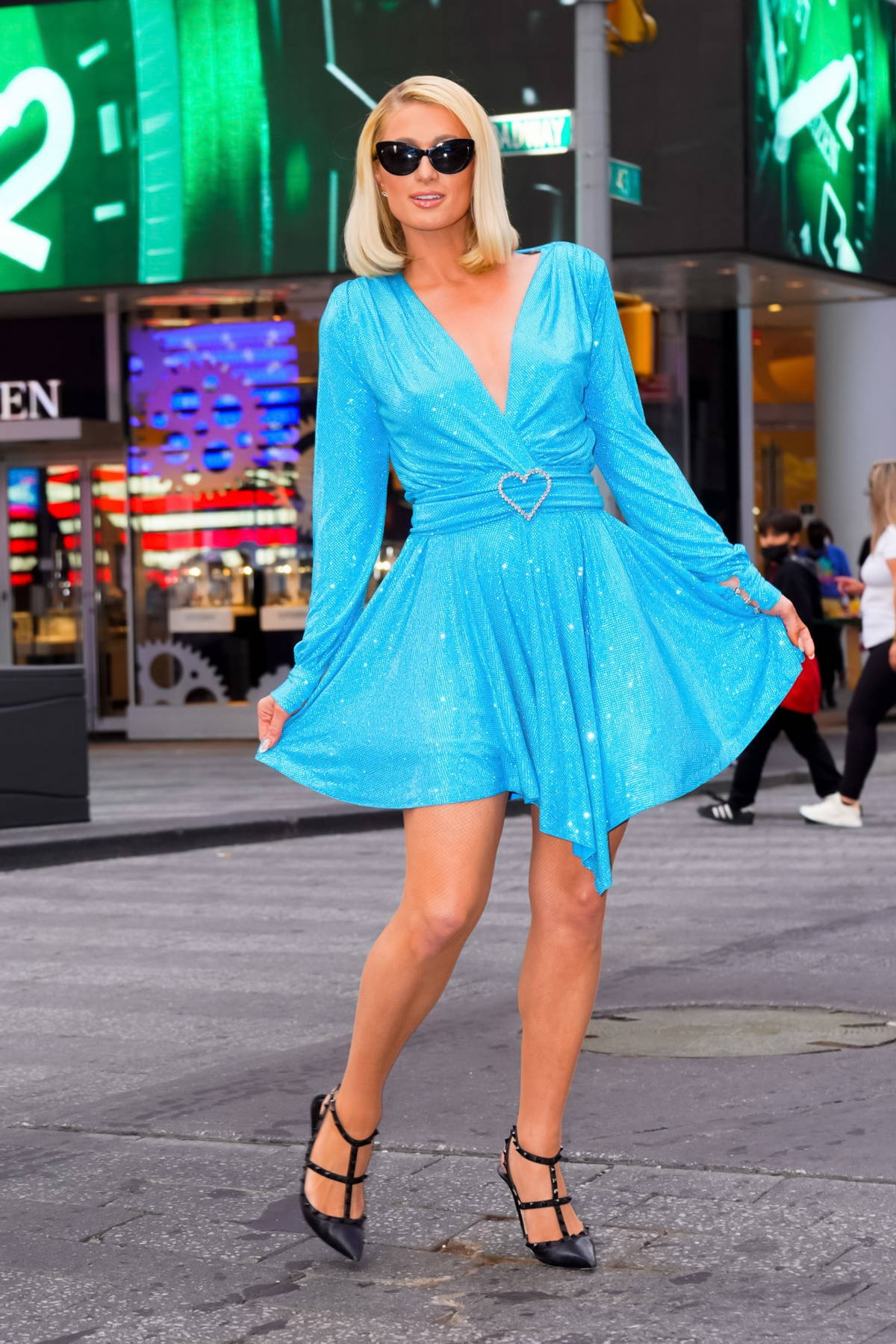 Paris Hilton dazzles in a sparkly blue dress while posing for photos at Times Square in New York City