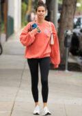 Sara Sampaio sports an orange sweatshirt and black leggings while leaving the gym in Los Angeles