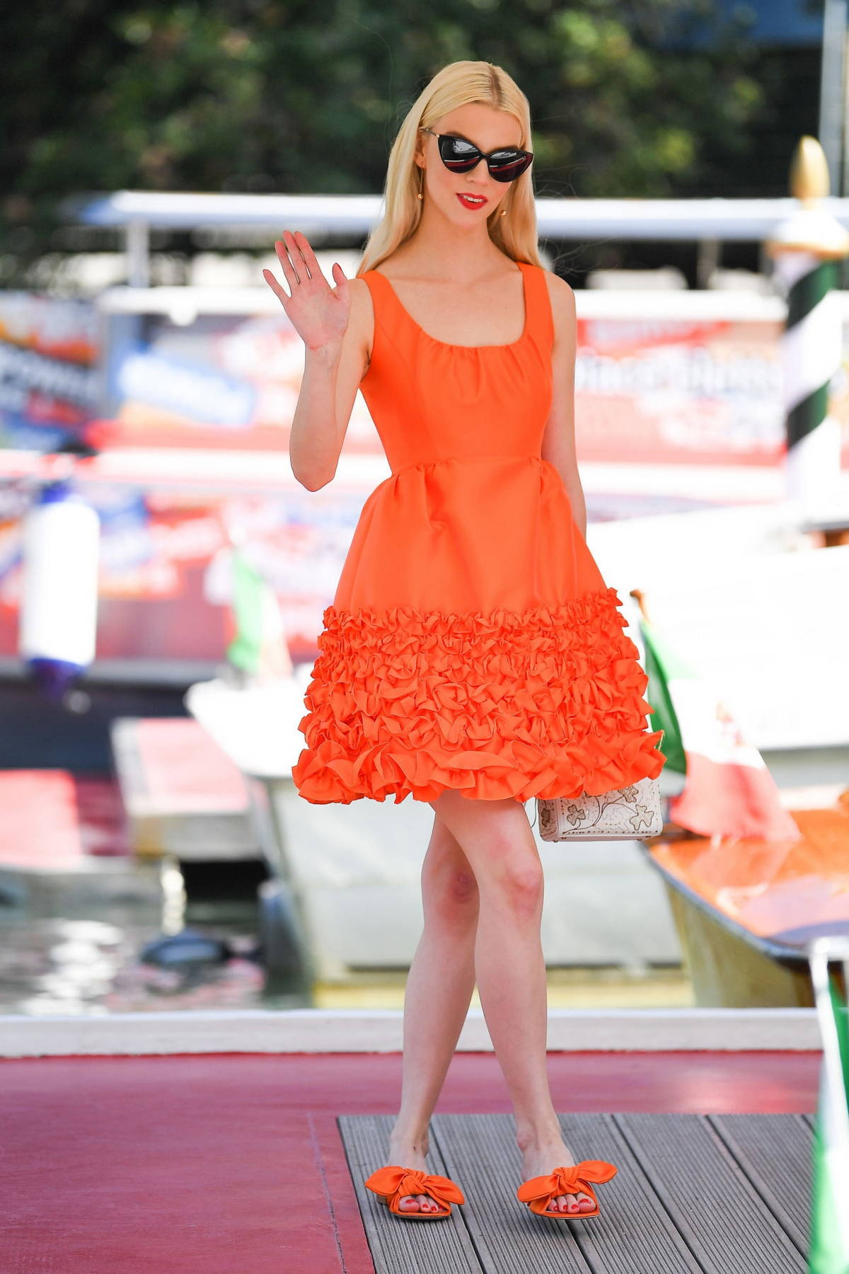 Anya Taylor-Joy looks cute in an orange dress while arriving at the 78th Venice International Film Festival in Venice, Italy