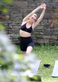 Bailee Madison shows off her fit physique in a black sports bra and legging shorts during an outdoor yoga session in upstate New York