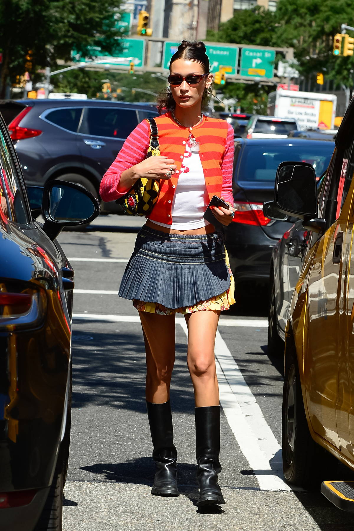 Bella Hadid looks stylish in a colorful cardigan and a mini skirt with black boots while stepping out in Soho, New York City
