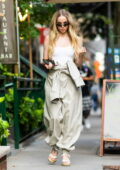 Dove Cameron looks trendy in a white corset top paired with a jumpsuit while out in Midtown, New York City