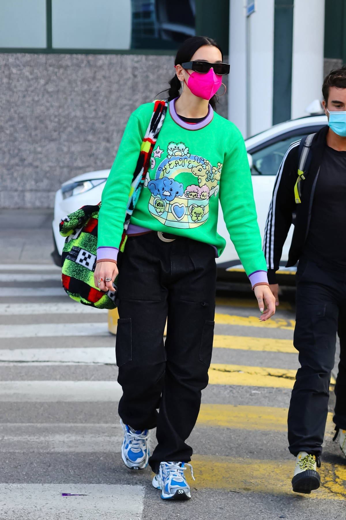 Dua Lipa stands out in a bright green sweater as she touches down in Milan for the Fashion Week, Italy