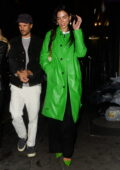 Dua Lipa stands out in a bright green trench coat with matching shoes while out for dinner with friends in London, UK