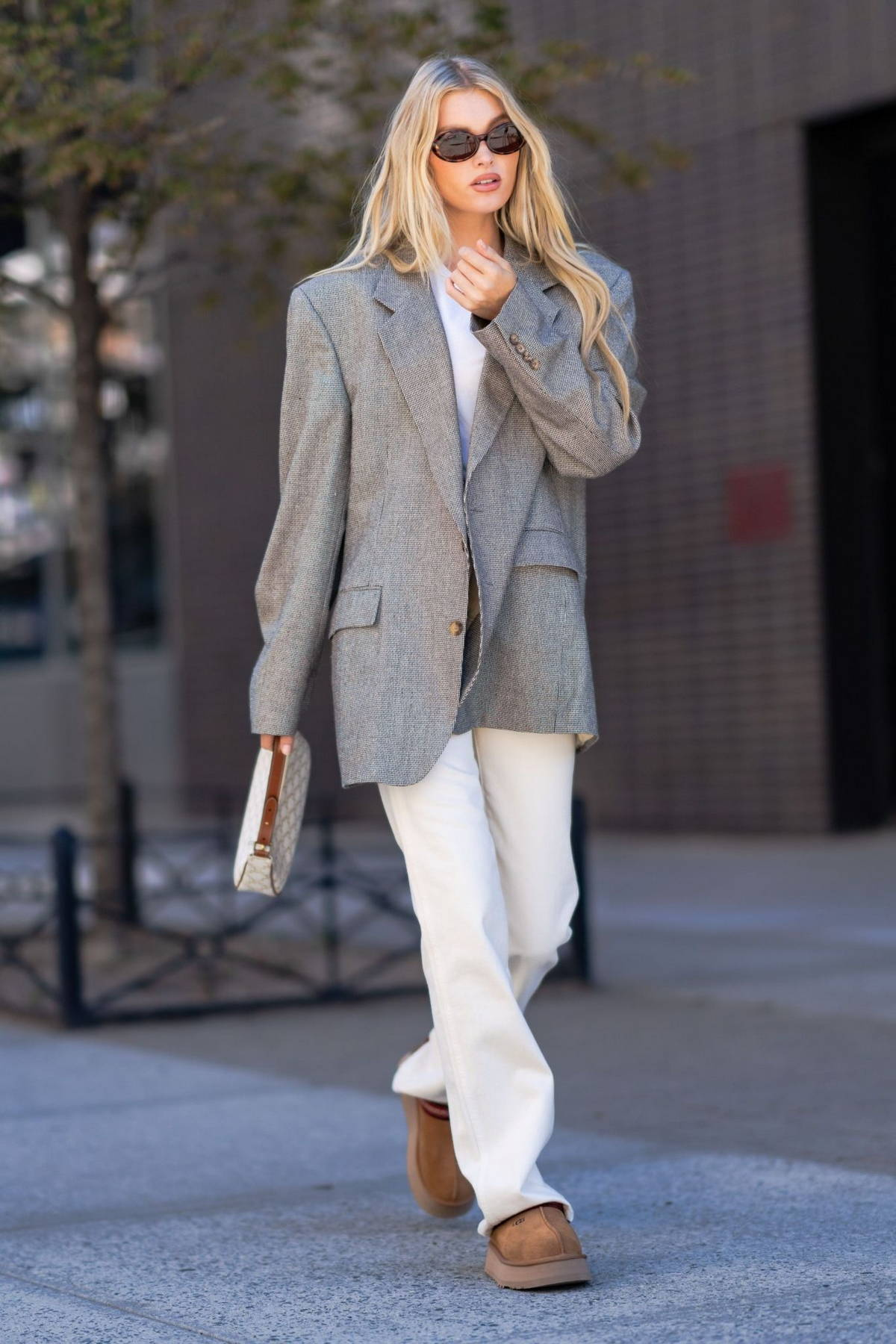 Elsa Hosk keeps it casual yet chic with a grey blazer, white top and cream trousers while out in SoHo, New York City