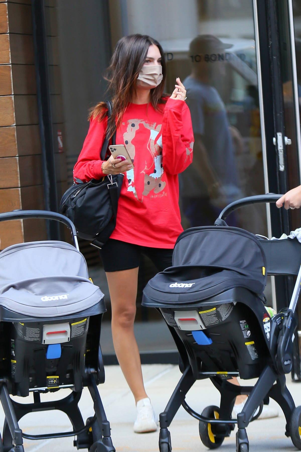 Emily Ratajkowski sports a red sweatshirt and black legging shorts while leaving Gigi Hadid's apartment in New York City