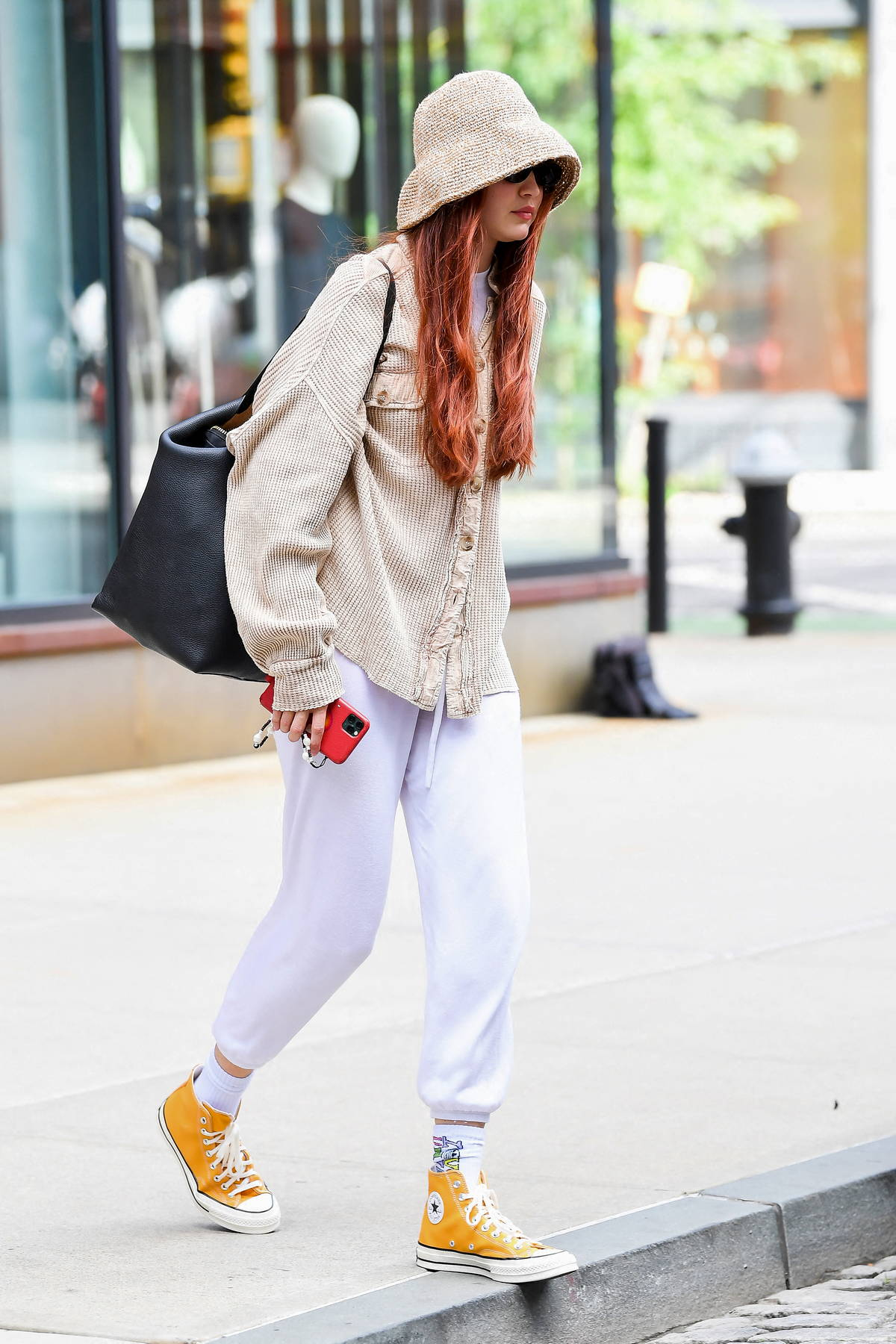 Gigi Hadid wears a bucket hat with a beige shirt, white joggers and yellow converse while heading out in New York City
