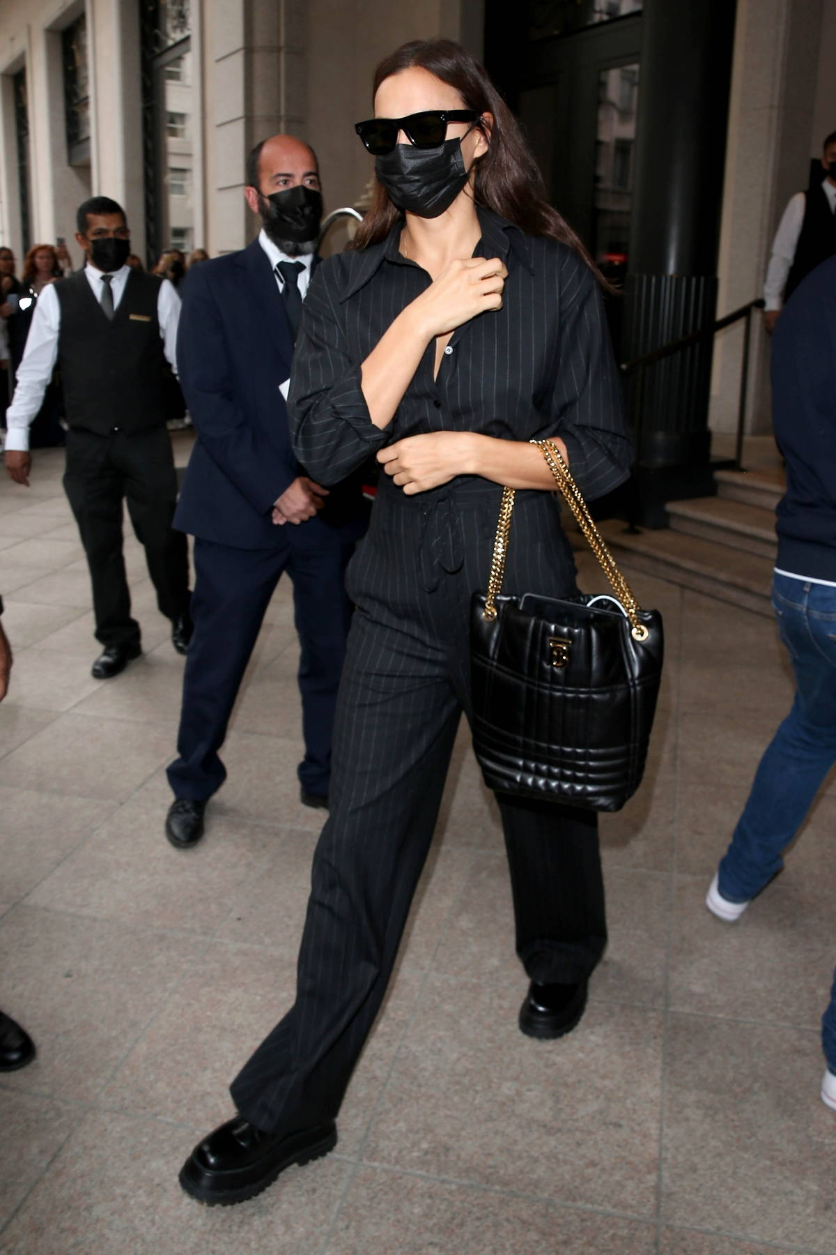 Irina Shayk seen wearing pinstriped dress pants and a matching shirt as she leaves her hotel in Milan, Italy