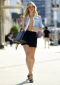 Joy Corrigan stuns in an unbuttoned top paired with black shorts during a photoshoot in New York City
