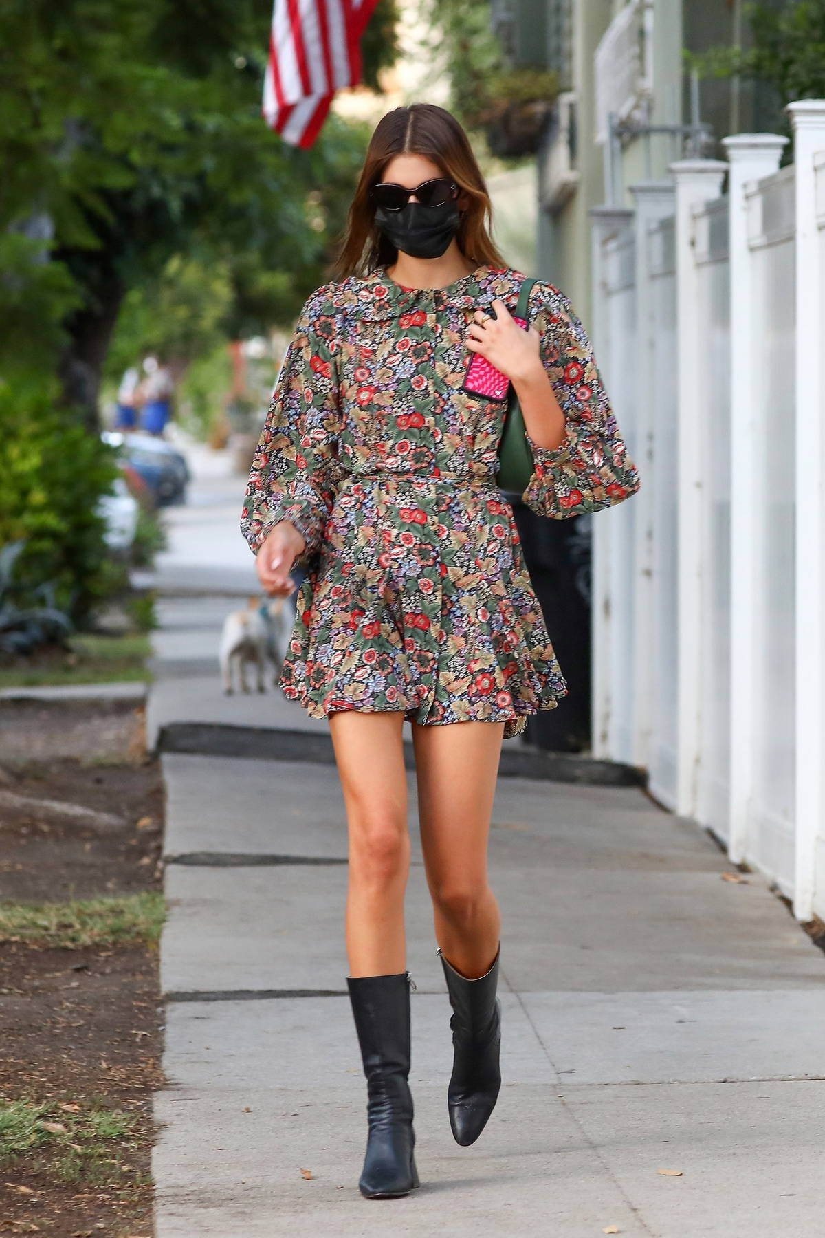 Kaia Gerber wears a floral print dress with black leather boots for dinner with friends in Silverlake, California