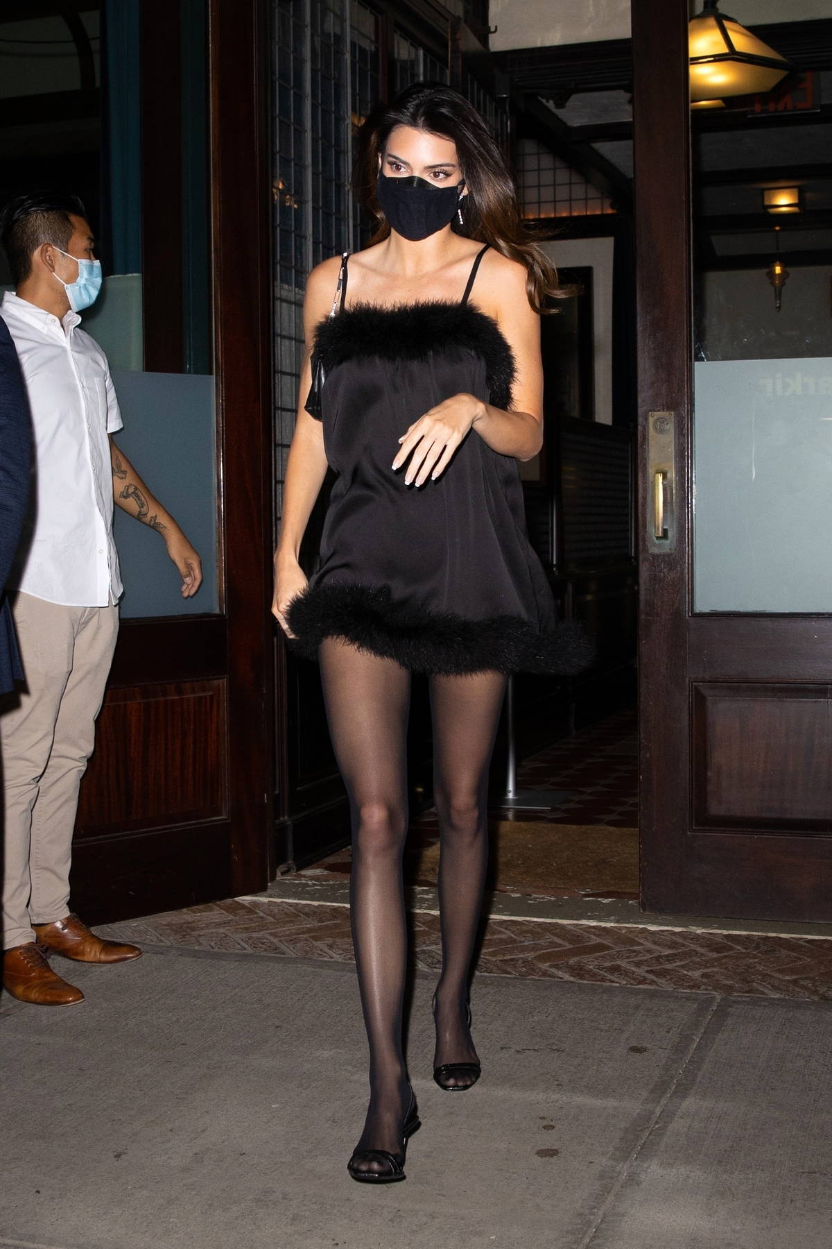 Kendall Jenner cuts a striking figure wearing a short black fur-lined dress as she heads out in New York City