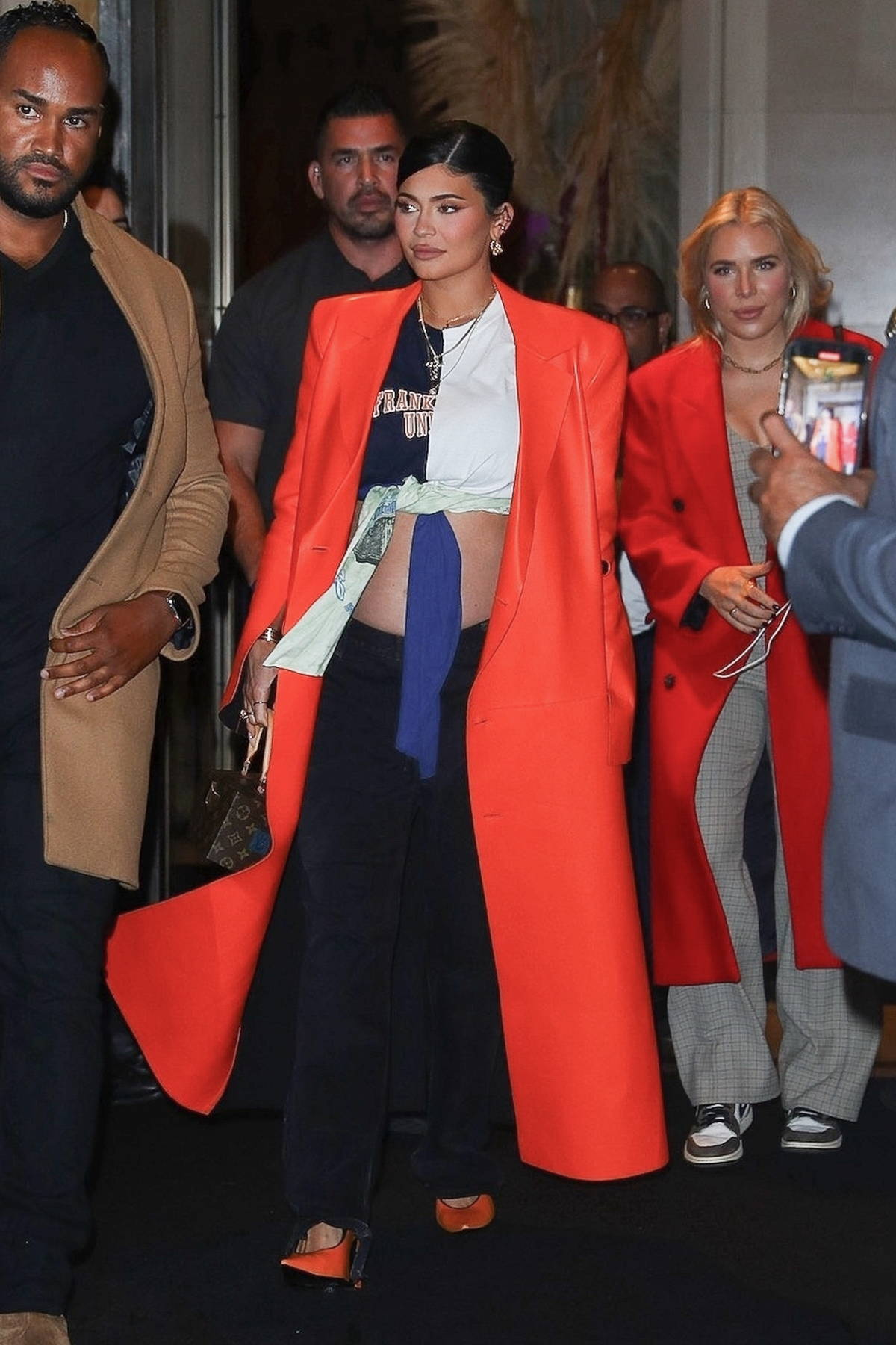 Kylie Jenner rocks a neon orange coat and shows off her belly on the way to dinner in New York City