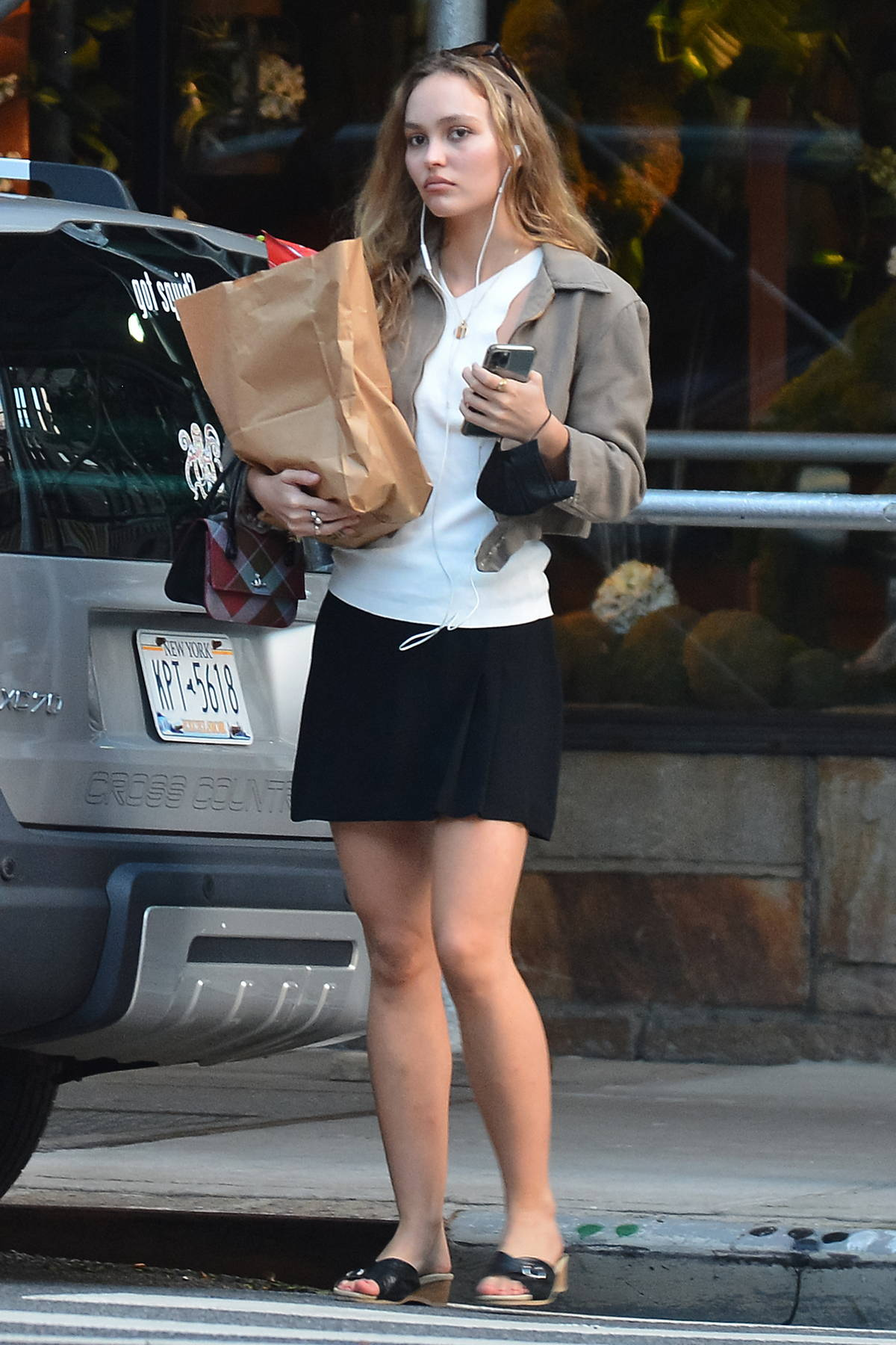 Lily-Rose Depp wears a black mini skirt with a white top while picking up some groceries in New York City