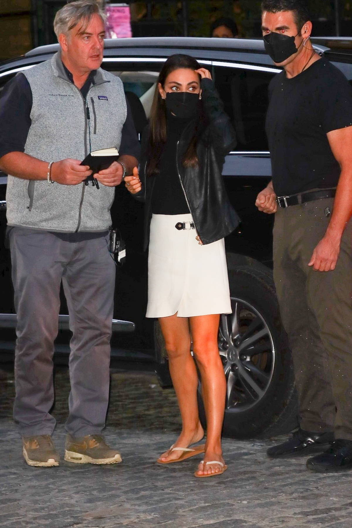 Mila Kunis seen wearing a white skirt, a leather jacket, and sandals while on set of 'Luckiest Girl Alive' in New York City