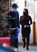 Olivia Munn displays her growing baby bump in a black form-fitting dress while out with boyfriend John Mulaney in New York City