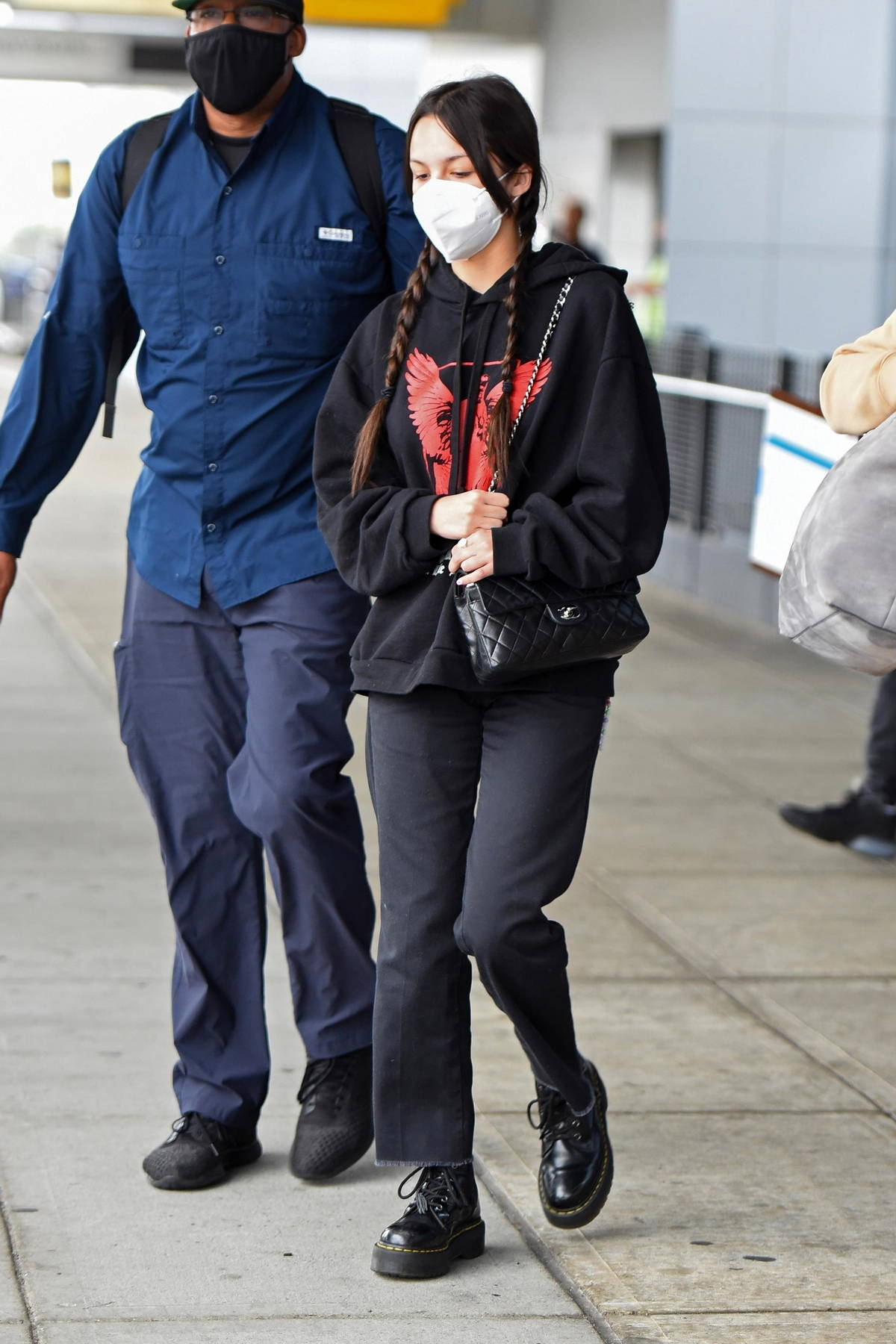 Olivia Rodrigo dons black jeans and a black hoodie while arriving at JFK airport in New York City