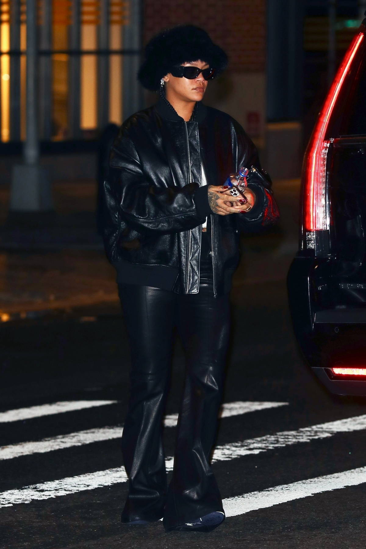 Rihanna dons all-black leather while stepping out for a chat with A$AP Rocky before returning to his place together in New York City