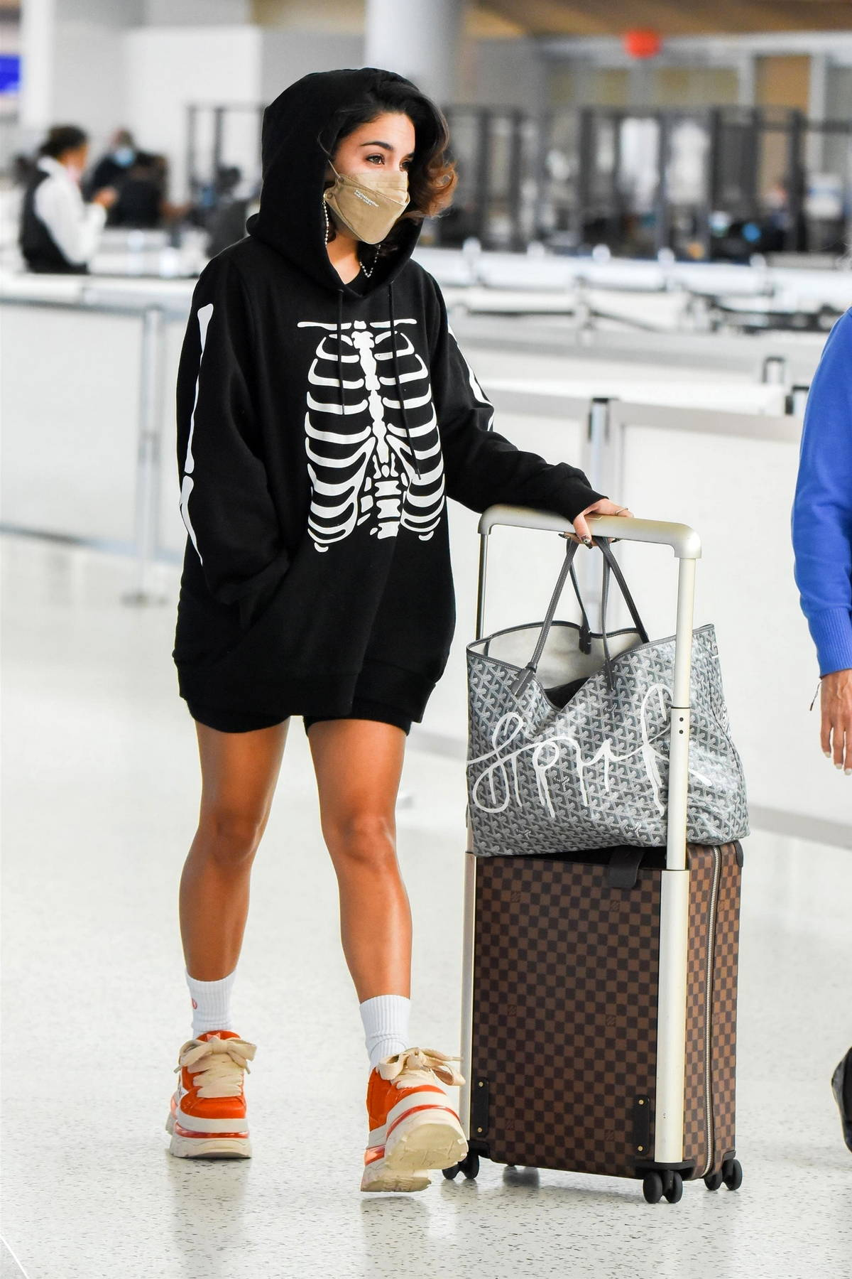 Vanessa Hudgens wears a skeleton print hoodie with legging shorts as she arrives at the JFK Airport in New York City