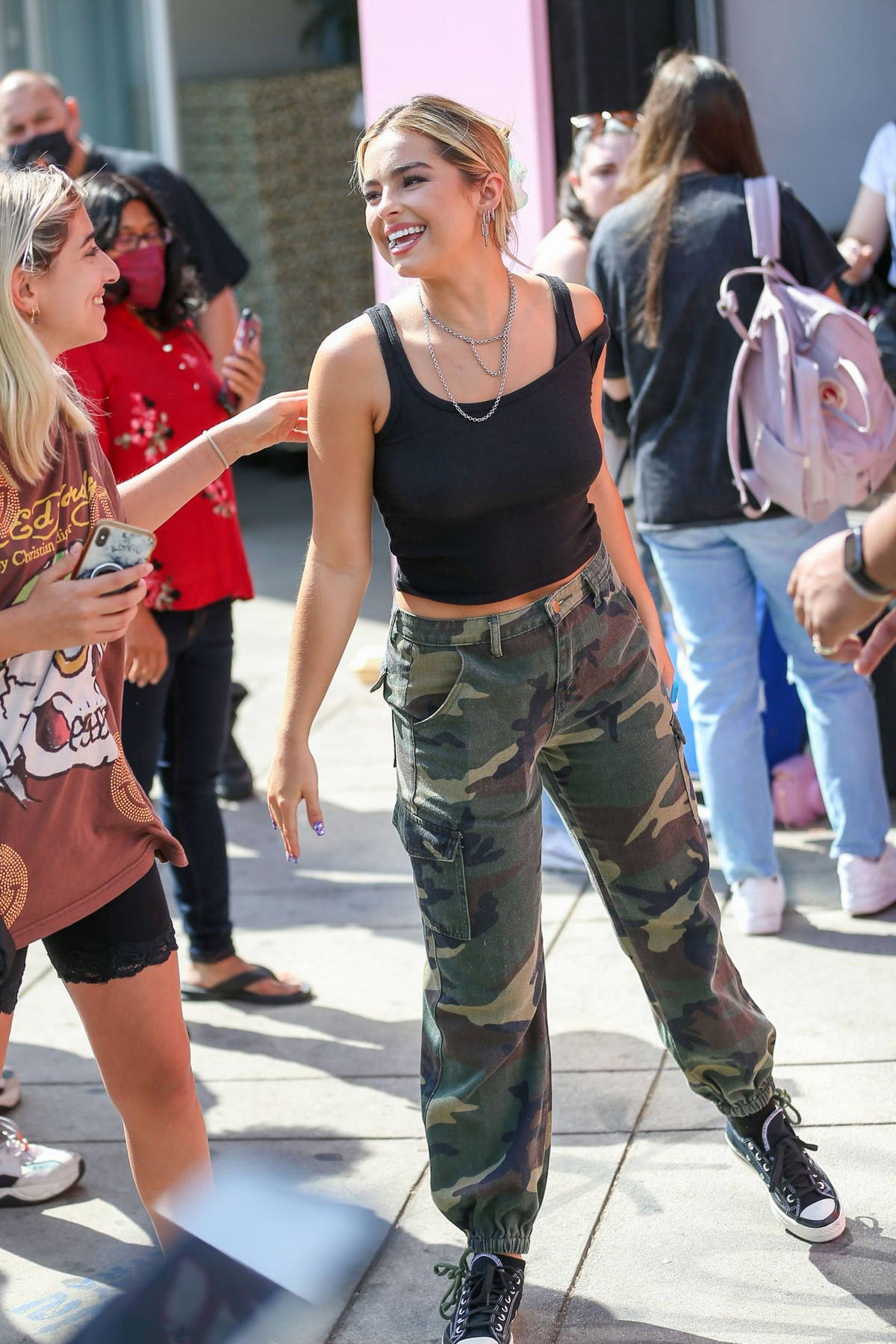 Addison Rae is all smiles while out wearing a black crop top and camouflage pants in Los Angeles