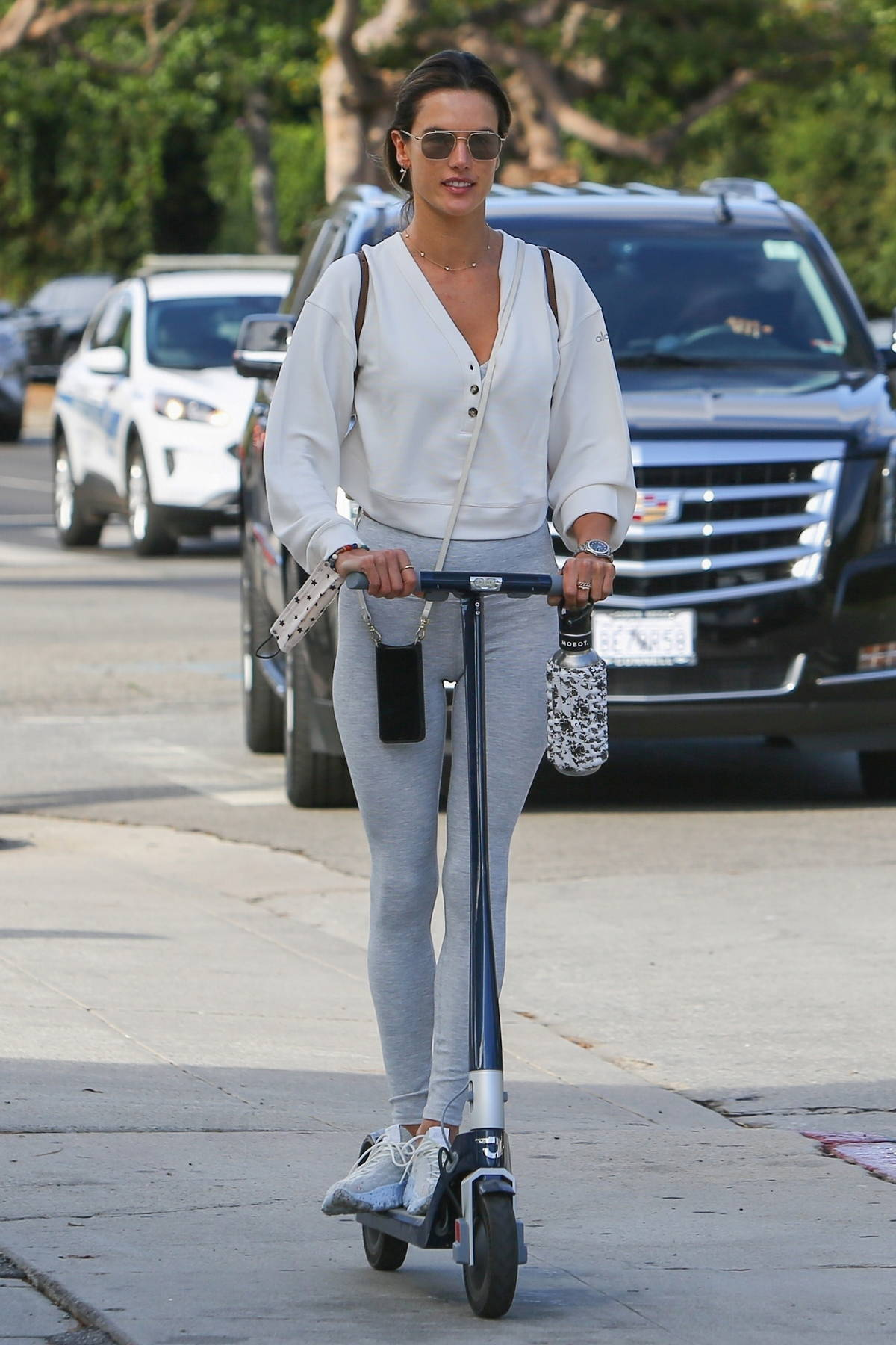 Alessandra Ambrosio looks amazing in a white blouse and grey leggings while riding a scooter to the gym in Brentwood, California