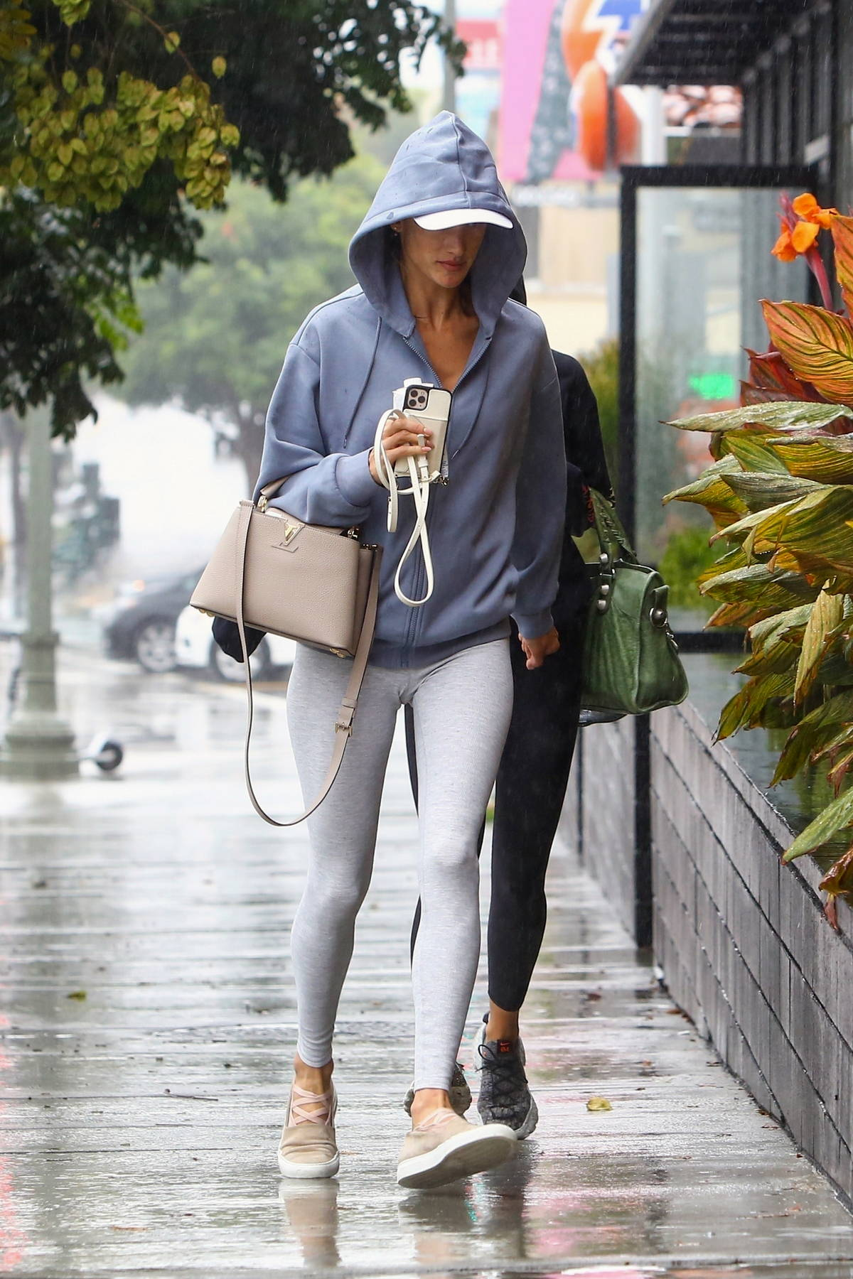 Alessandra sports a hoodie and leggings as she braves the rain while heading to a Pilates class in Santa Monica, California