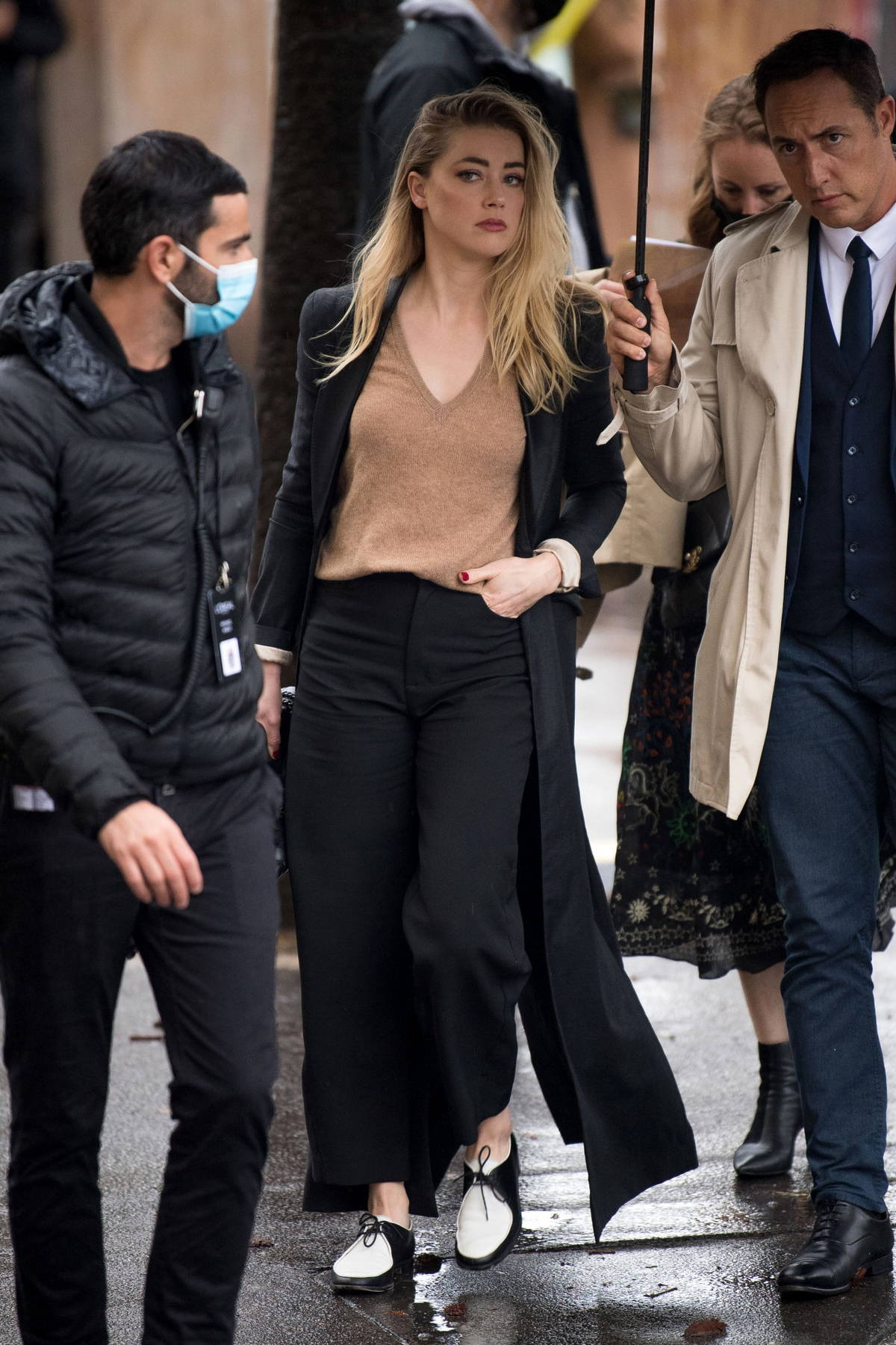 Amber Heard looks chic in a black trench coat with matching trousers and a beige sweater while out in Paris, France