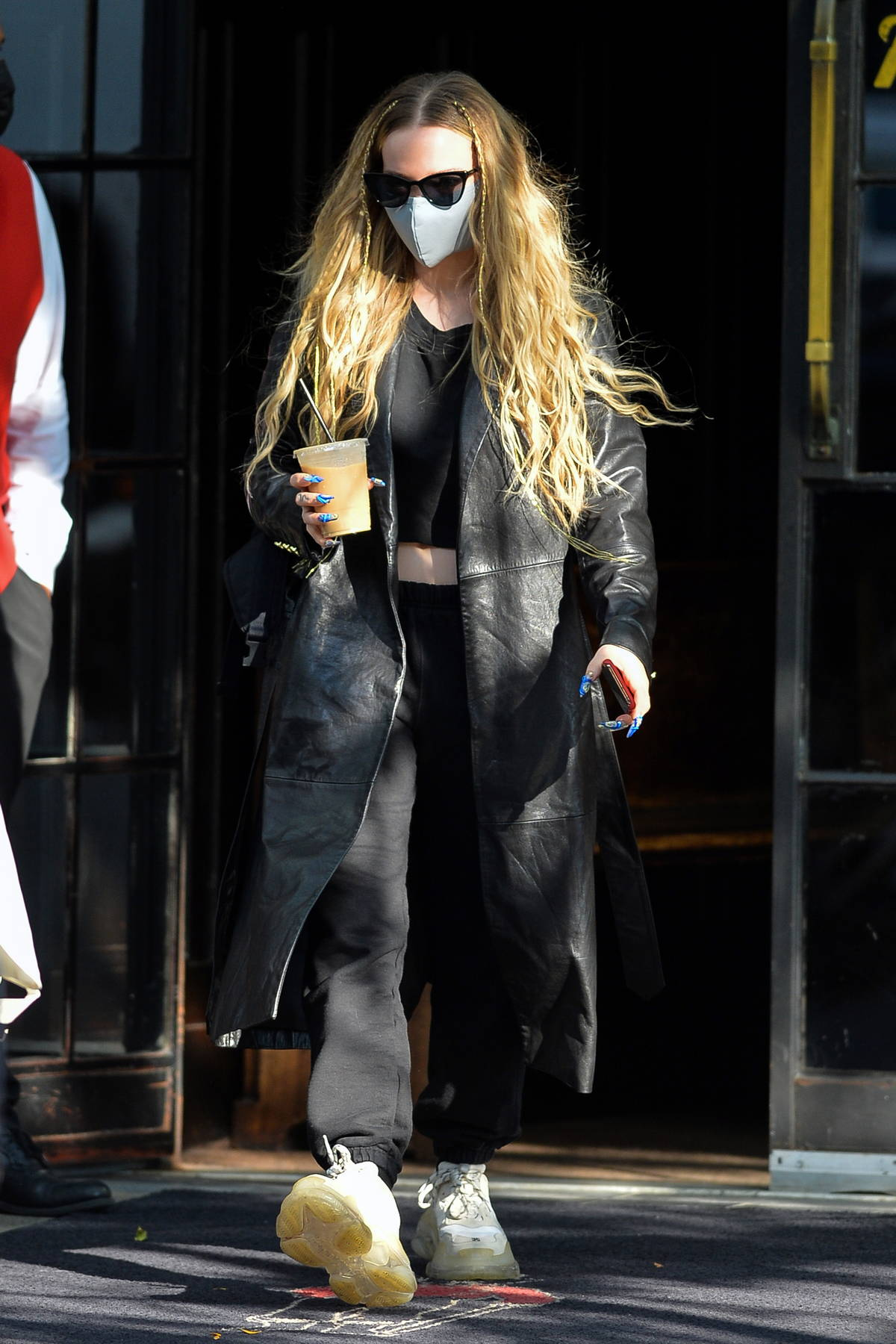 Dove Cameron rocks a leather trench coat over black sweats while heading out holding an iced coffee in New York City
