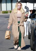 Hilary Duff bundles up in a knitted long coat over a tank top and leggings while making her morning coffee run in Los Angeles