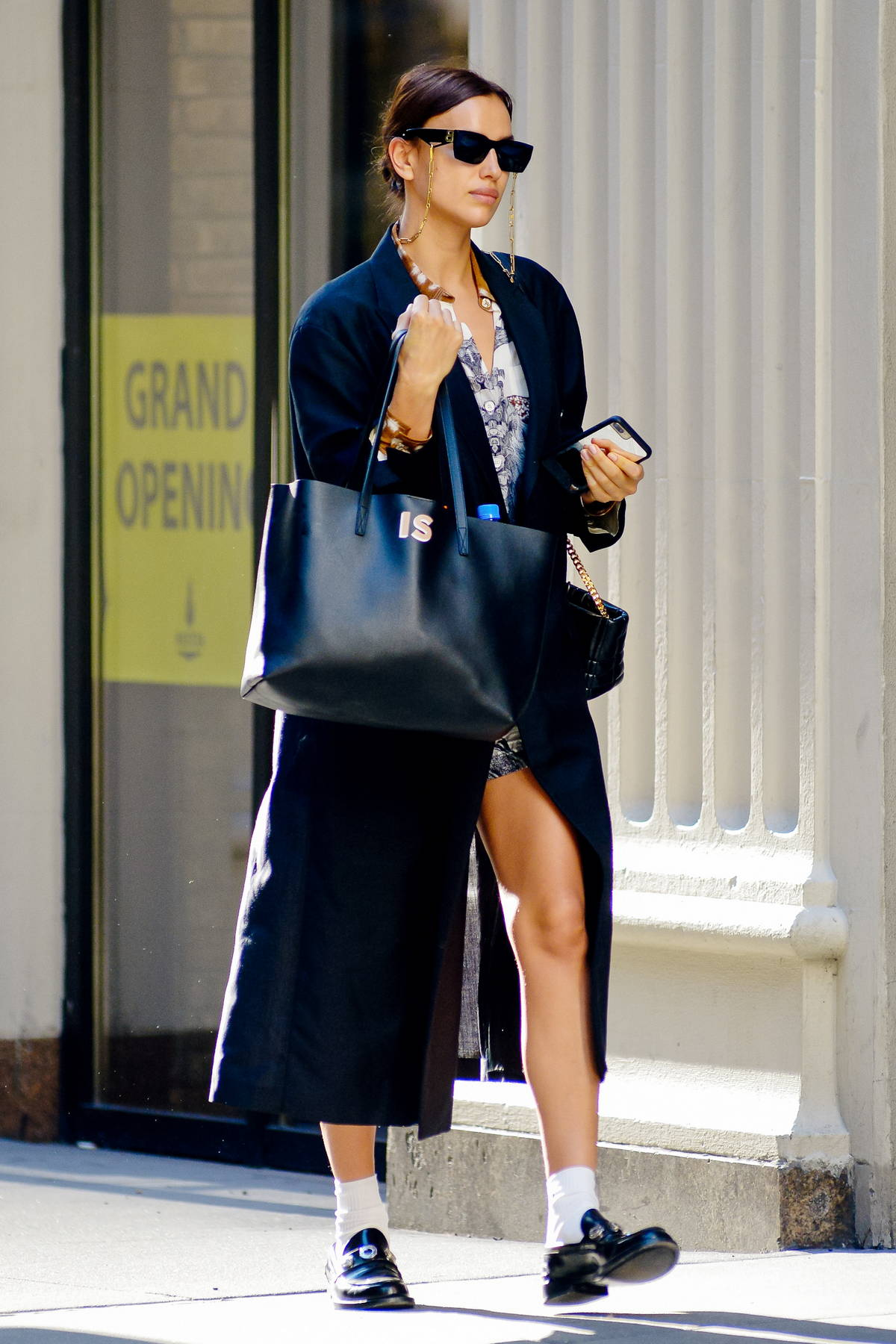 Irina Shayk looks super chic in a black trench coat over a mini dress while out in New York City