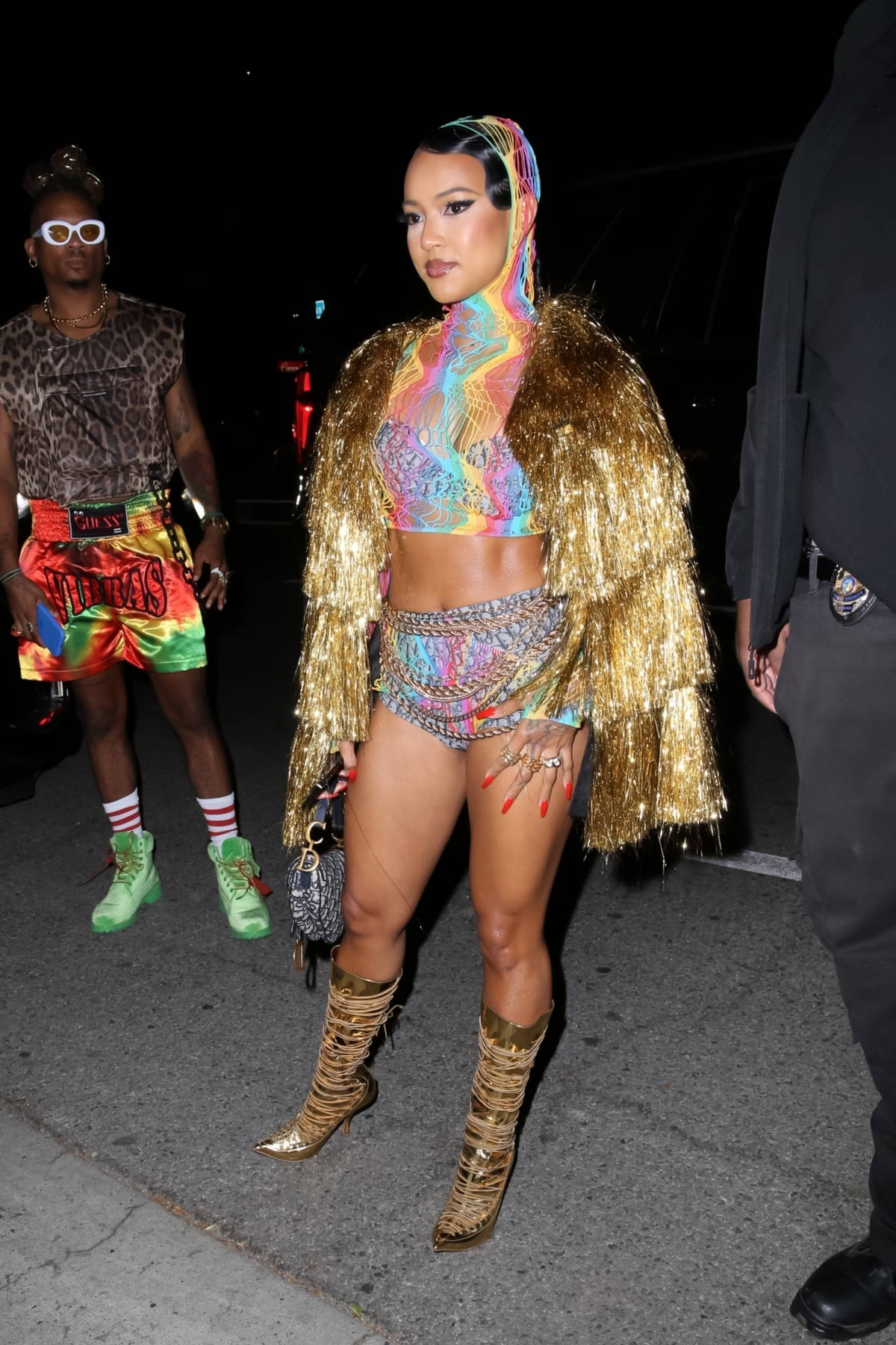 Karrueche Tran dazzles in a gold fringe coat with a colorful net outfit while attending Cardi b's 29th birthday party in Los Angeles