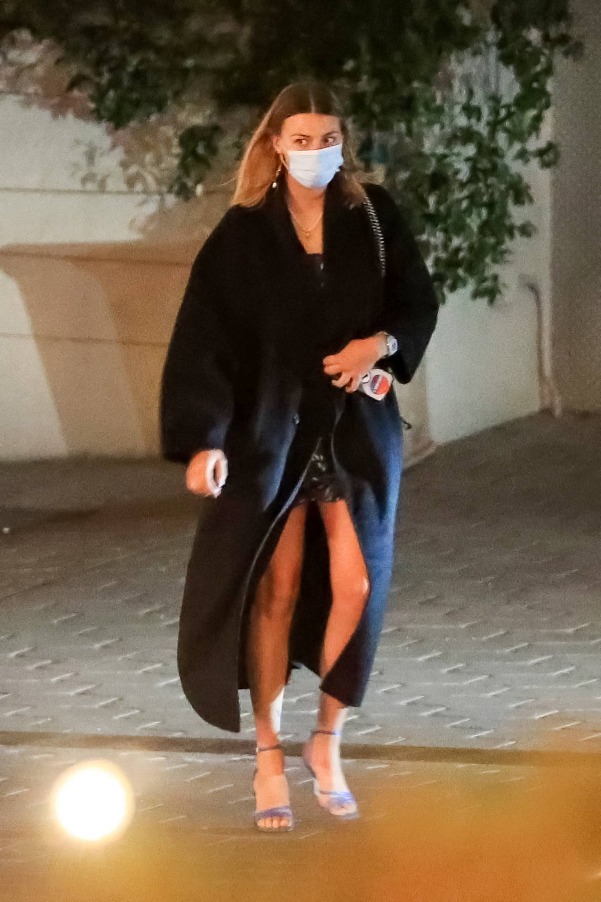Margot Robbie bundles up in a black overcoat while out for dinner in Los Angeles