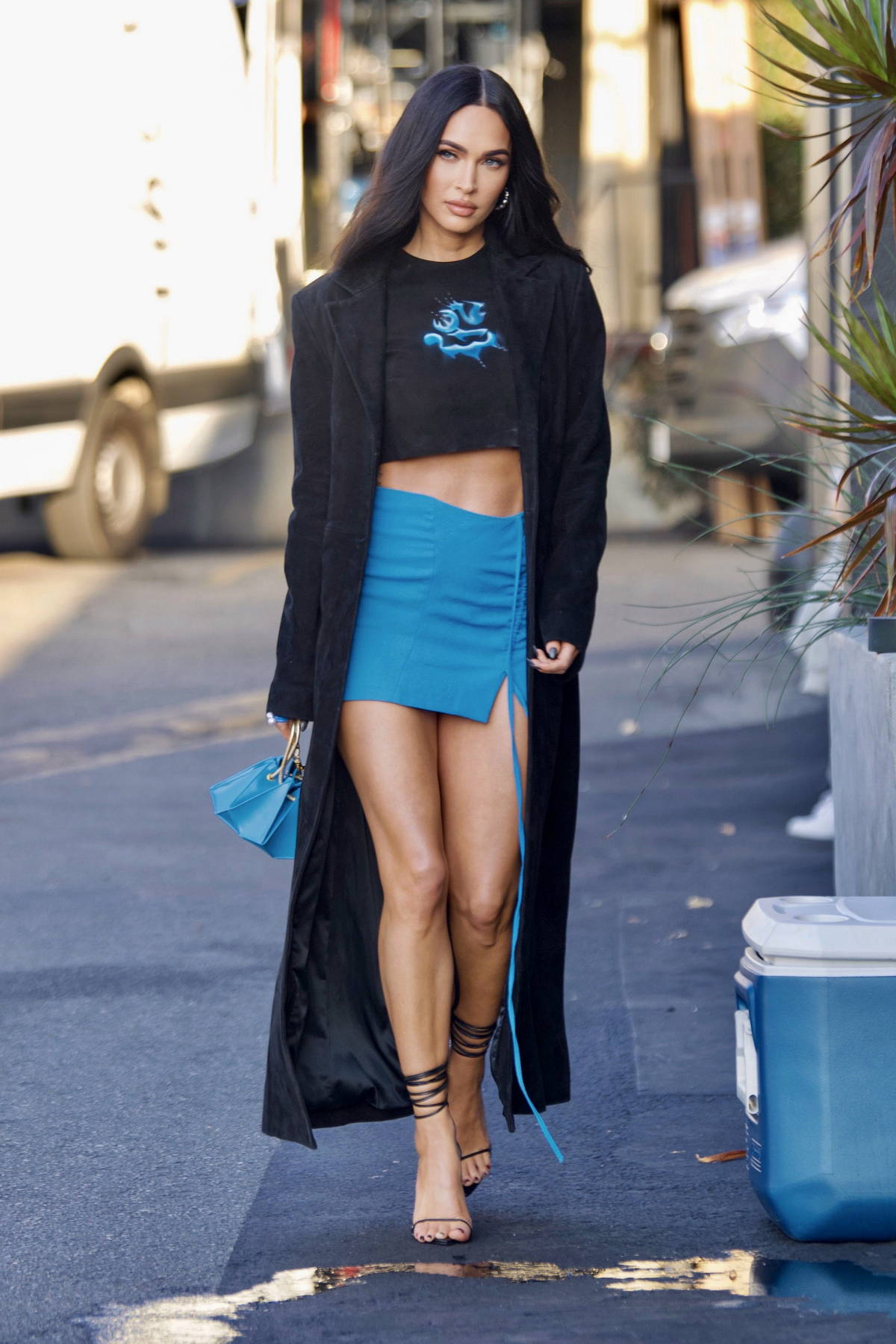 Megan Fox looks stunning in a blue mini skirt with a crop top and long black coat in Beverly Hills, California