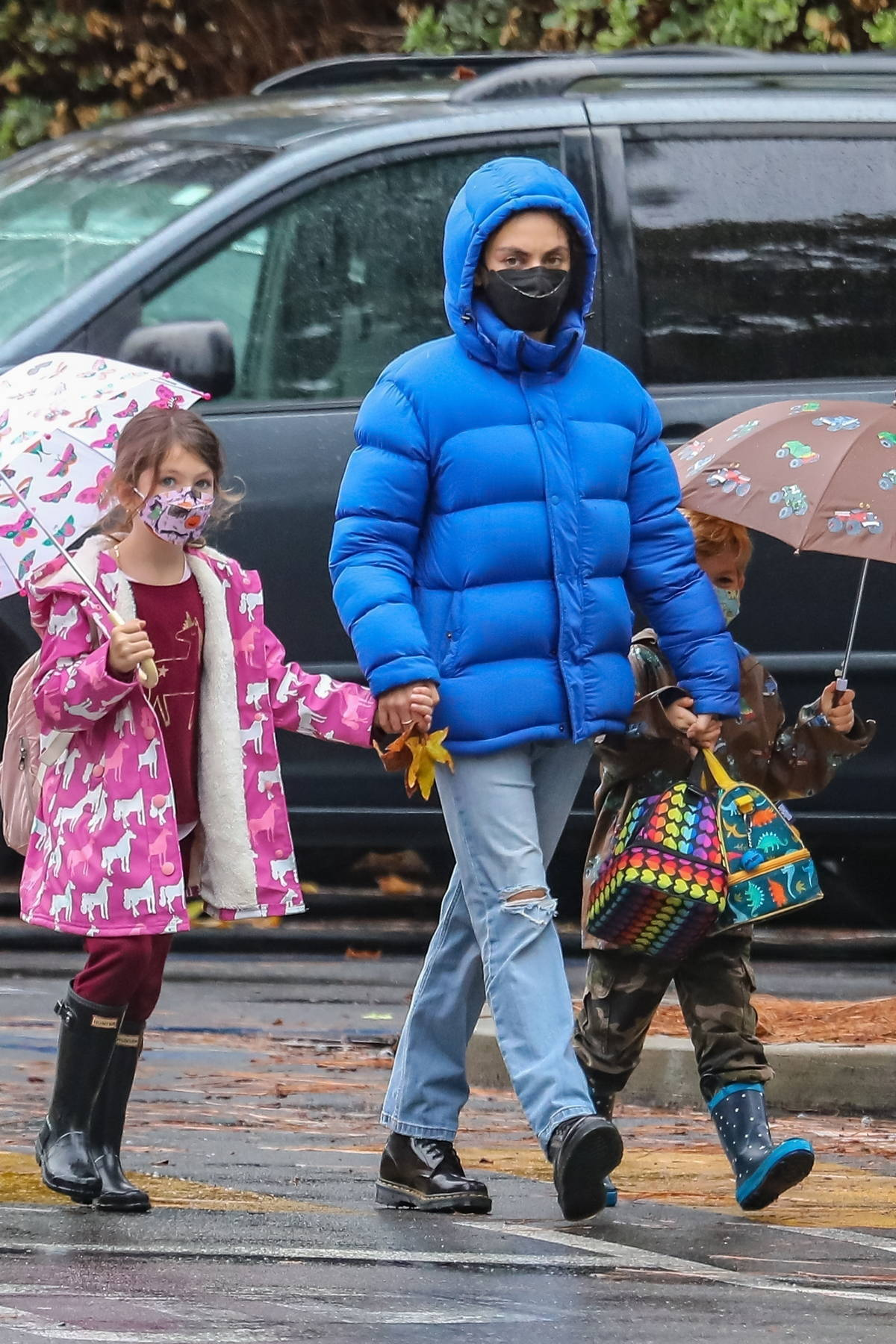 Mila Kunis wears a puffy blue rain jacket as she steps out in the rain with her kids in Santa Monica, California