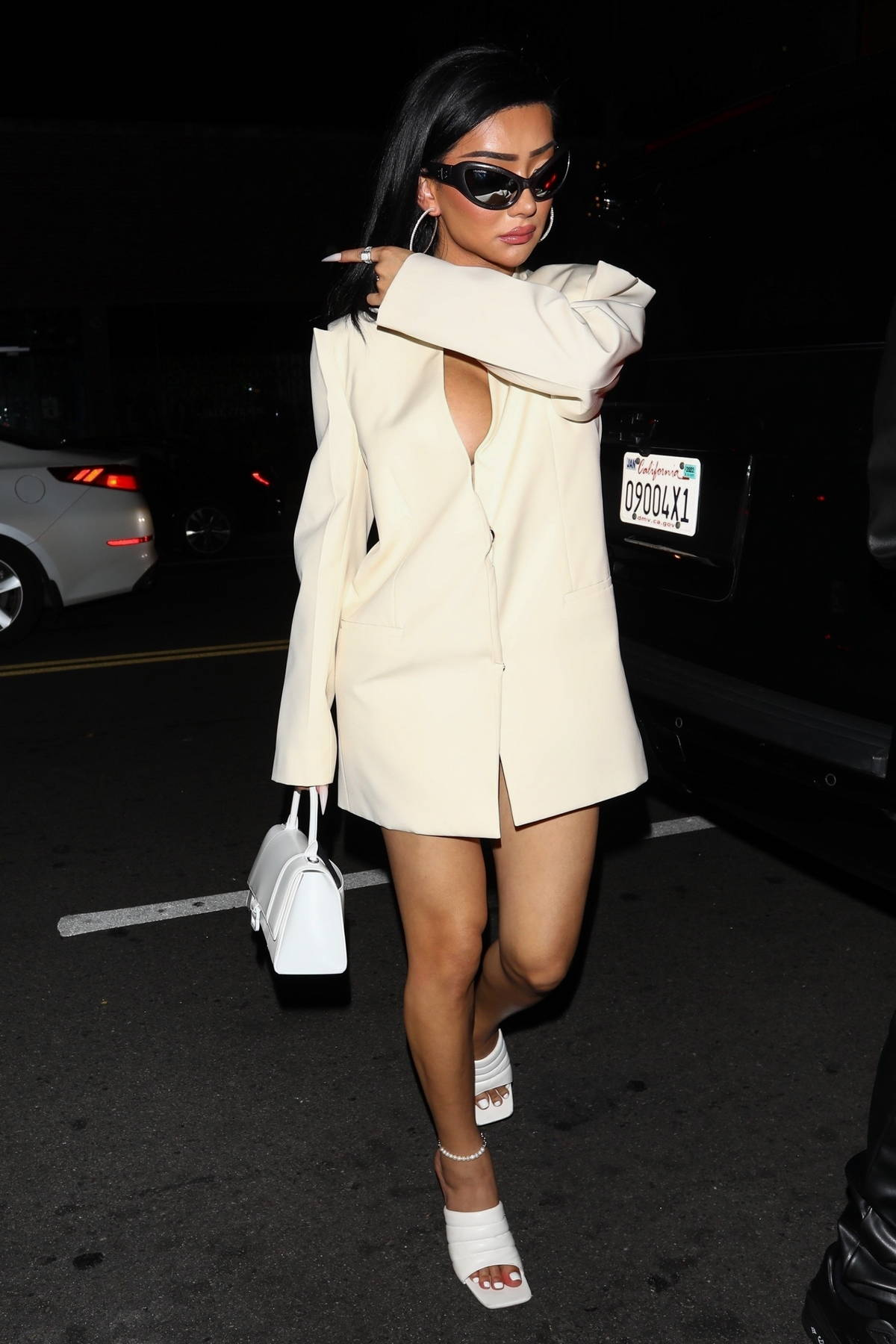 Nikita Dragun wears her sunglasses and a low-cut oversized blazer to Drake's 35th birthday party in Los Angeles