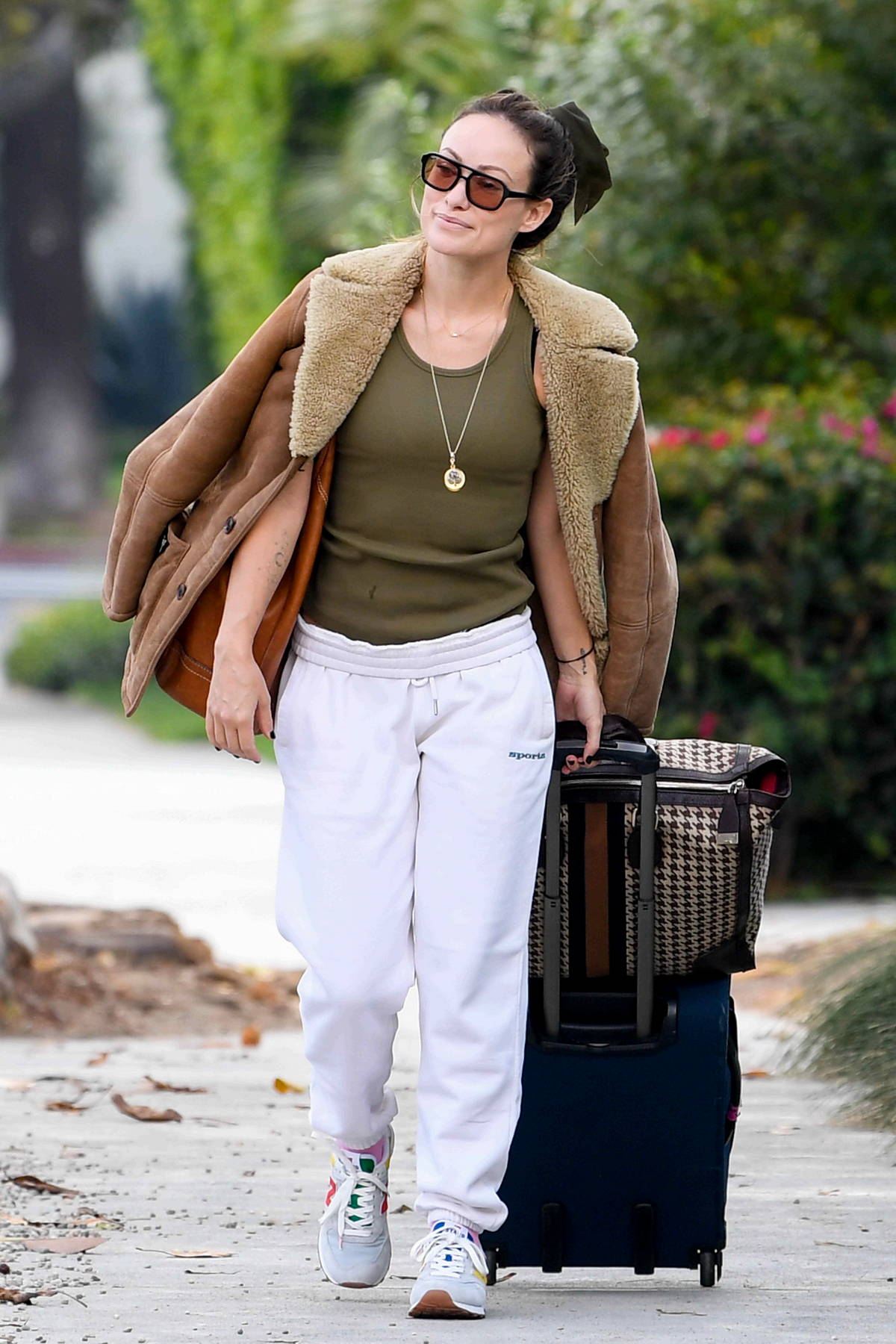Olivia Wilde rocks an army green tank top and white sweatpants while heading out with her luggage in Los Angeles